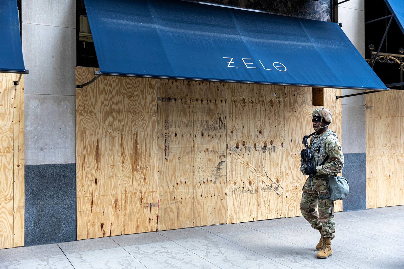 A member of the National Guard walks past a boarded up store front as he patrol downtown Minneapolis on April 14.