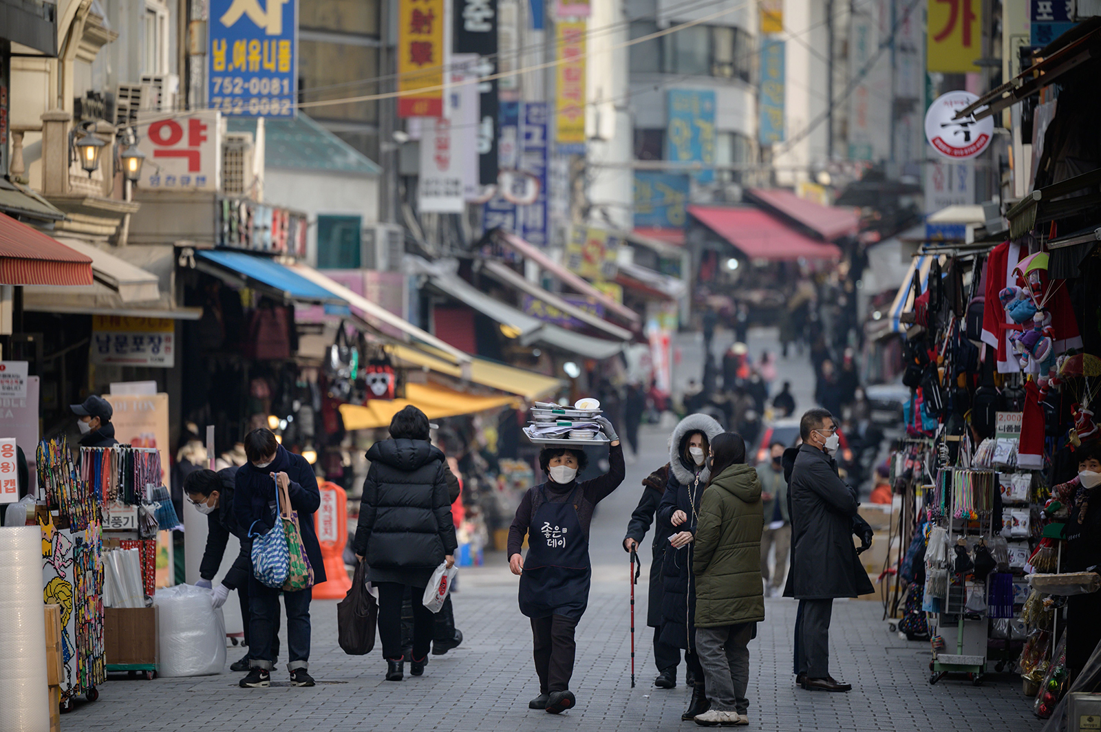 A restaurant worker carries a tray of food through Namdaemun market in Seoul, South Korea, on December 1.