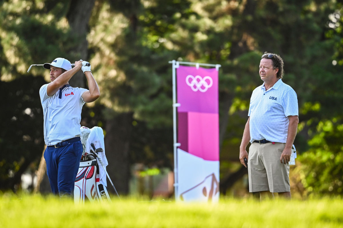 Schauffele hits balls on the practice range as his father, Stefan, looks on following the third round of Individual Stroke Play Golf on July 31.