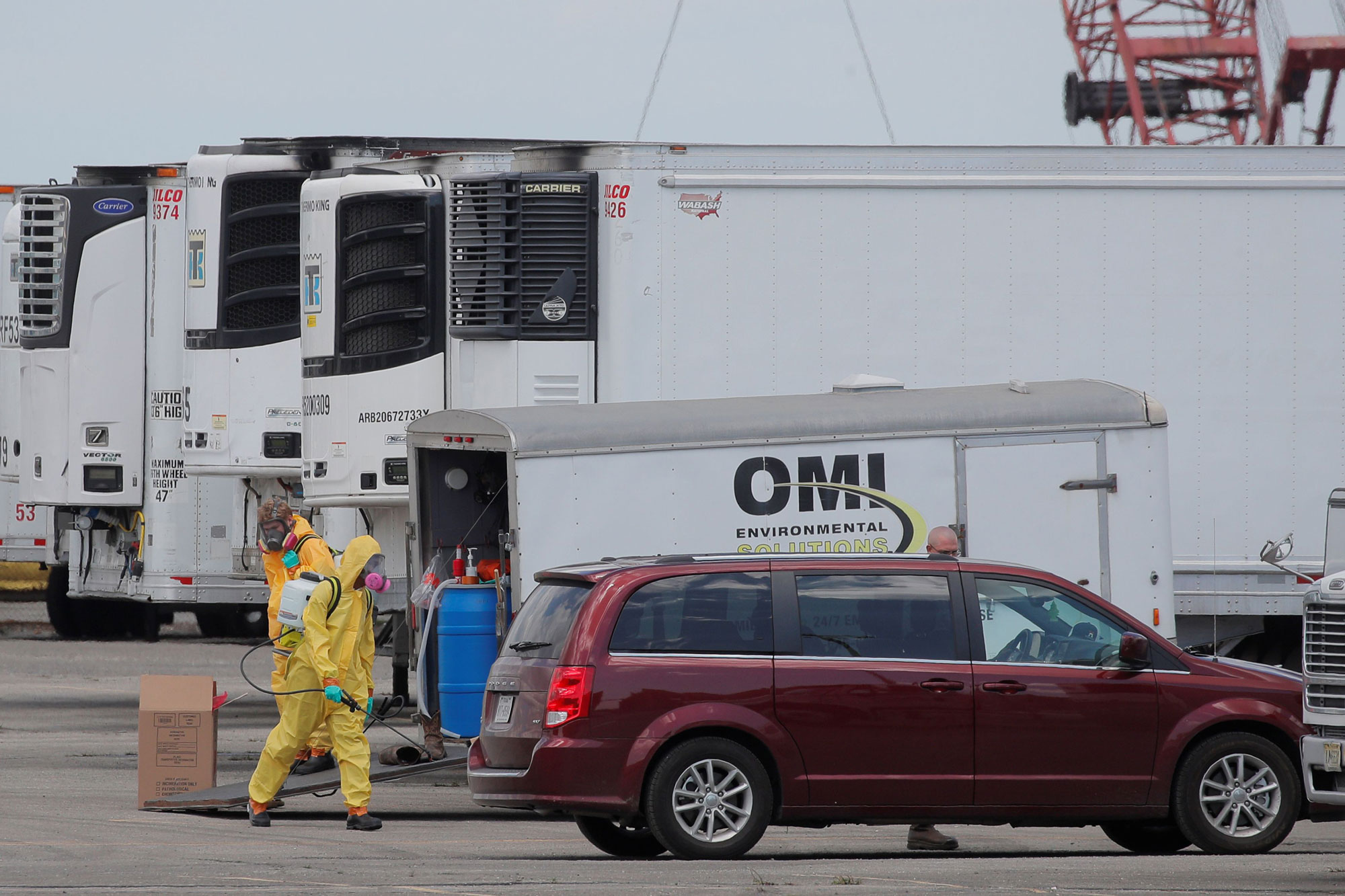 Workers are seen next to refrigerated tractor trailers that are being used to store bodies of deceased people at a temporary morgue in the Brooklyn borough of New York City, on May 4.