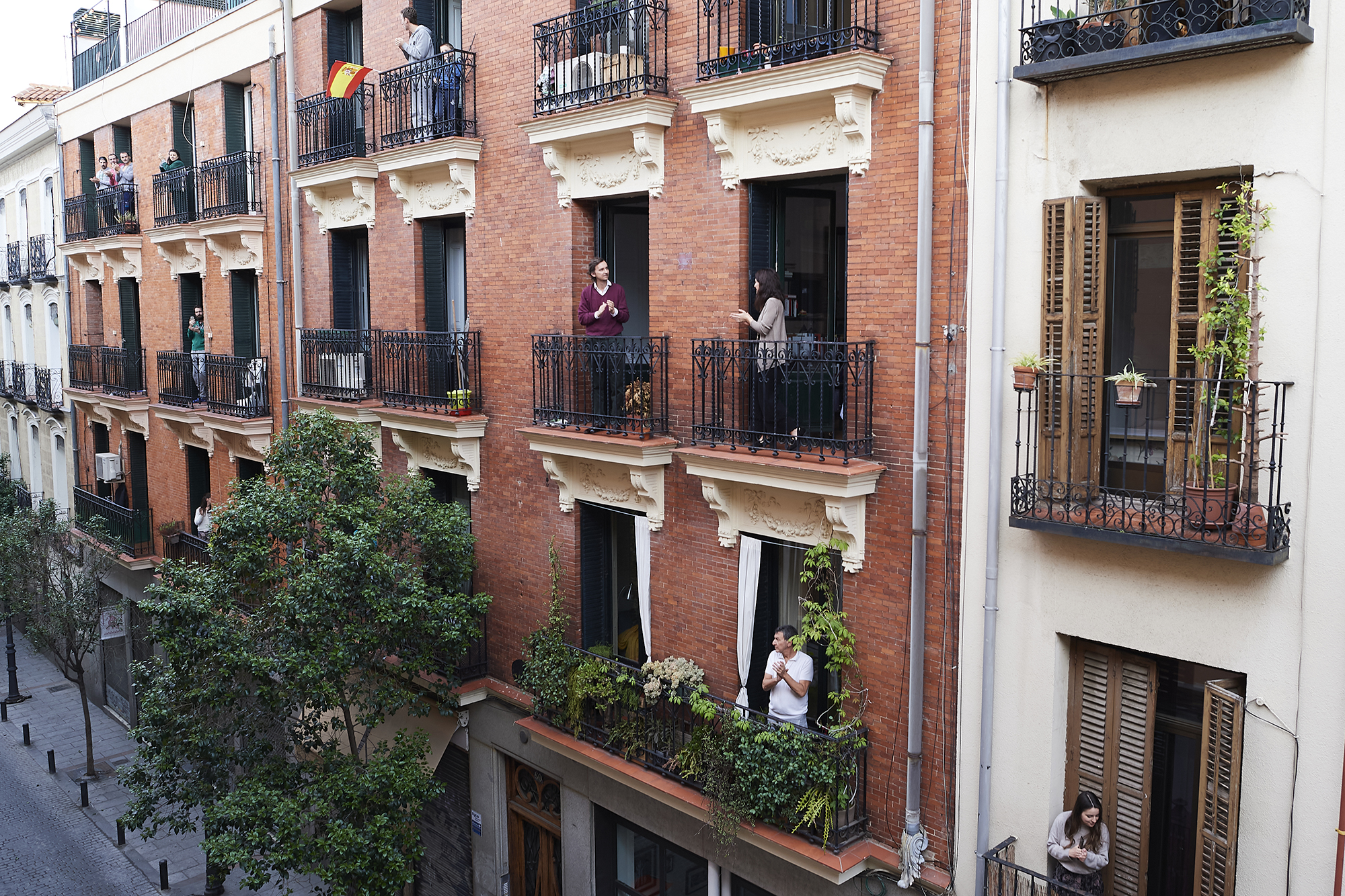 People on their balconies applaud to pay tribute to healthcare workers struggling to fight the coronavirus pandemic on Saturday, April 18, in Madrid.