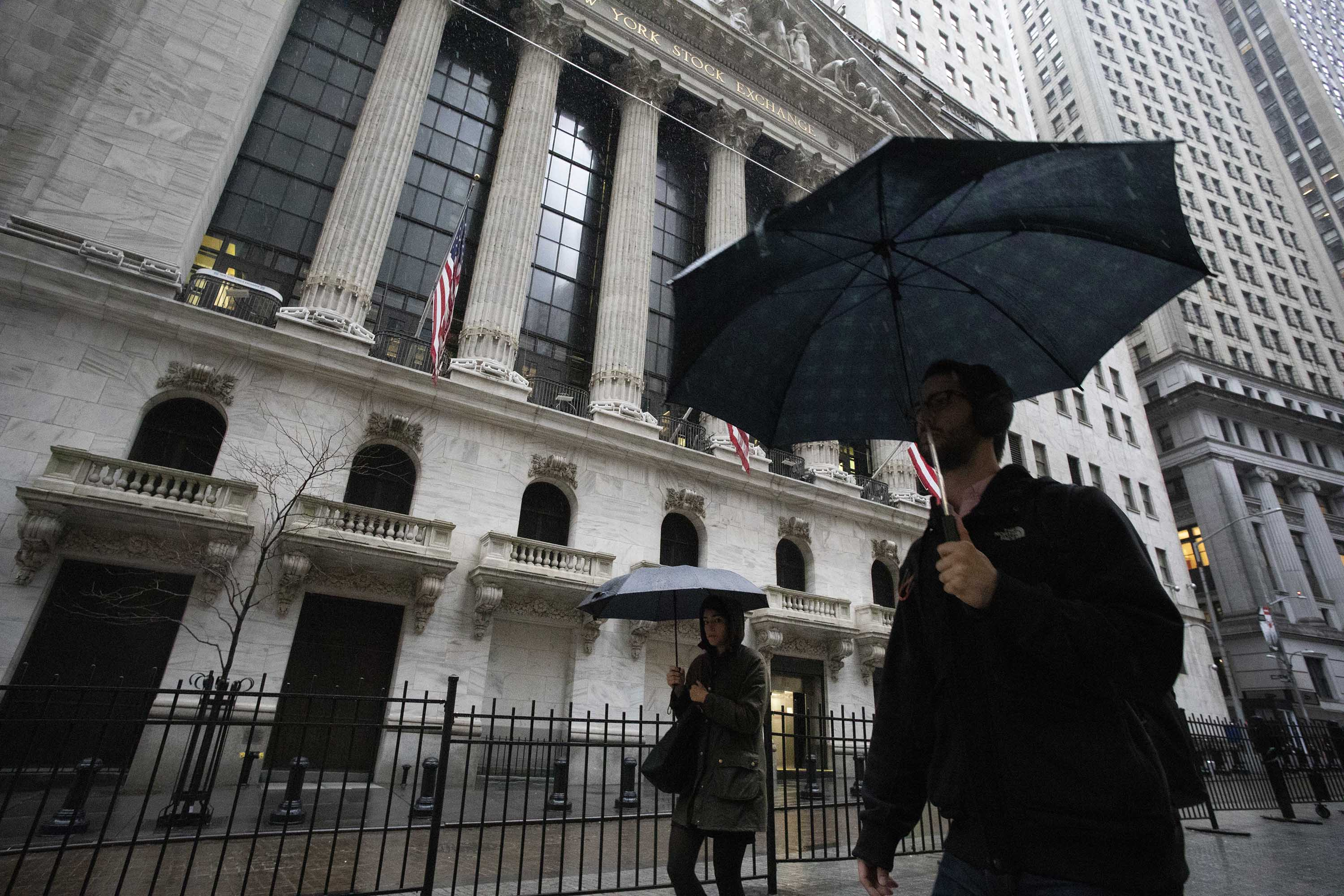 Pedestrians pass the New York Stock Exchange on Friday.