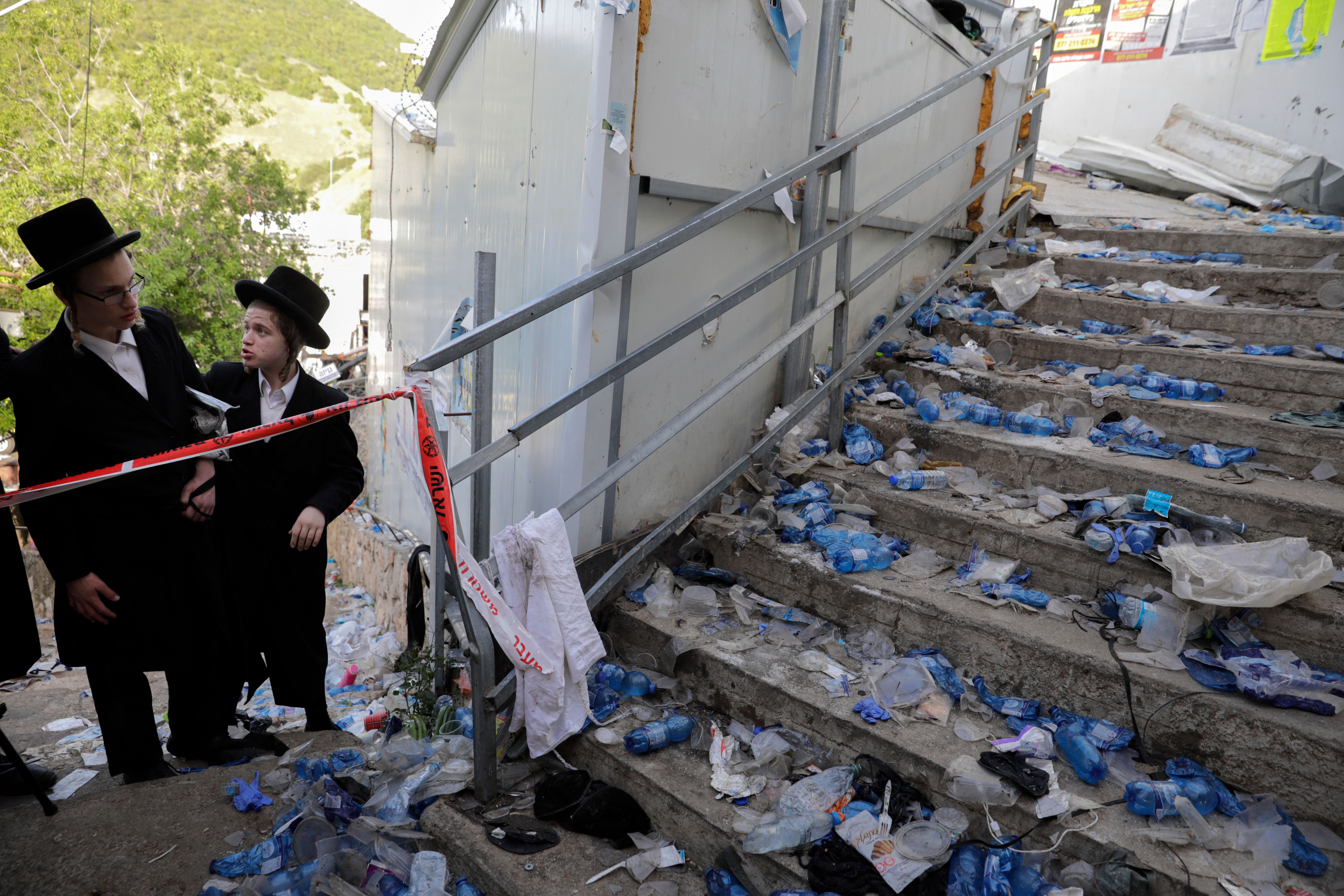 Ultra-Orthodox Jews look at the scene on April 30 following the Lag B'Omer festival on Mount Meron in Israel.