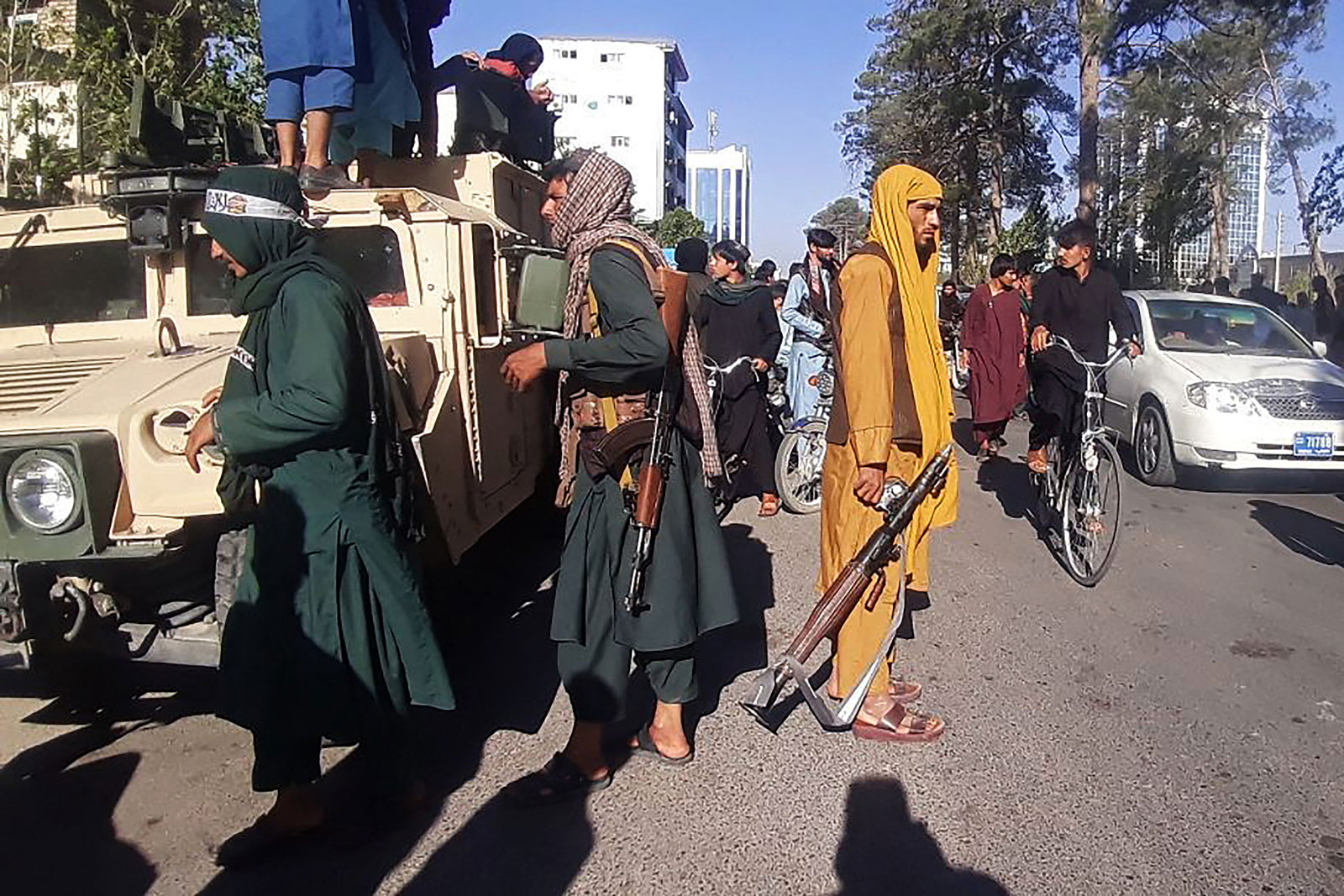 Taliban fighters stand guard along the road in Herat, Afghanistan on August 13.
