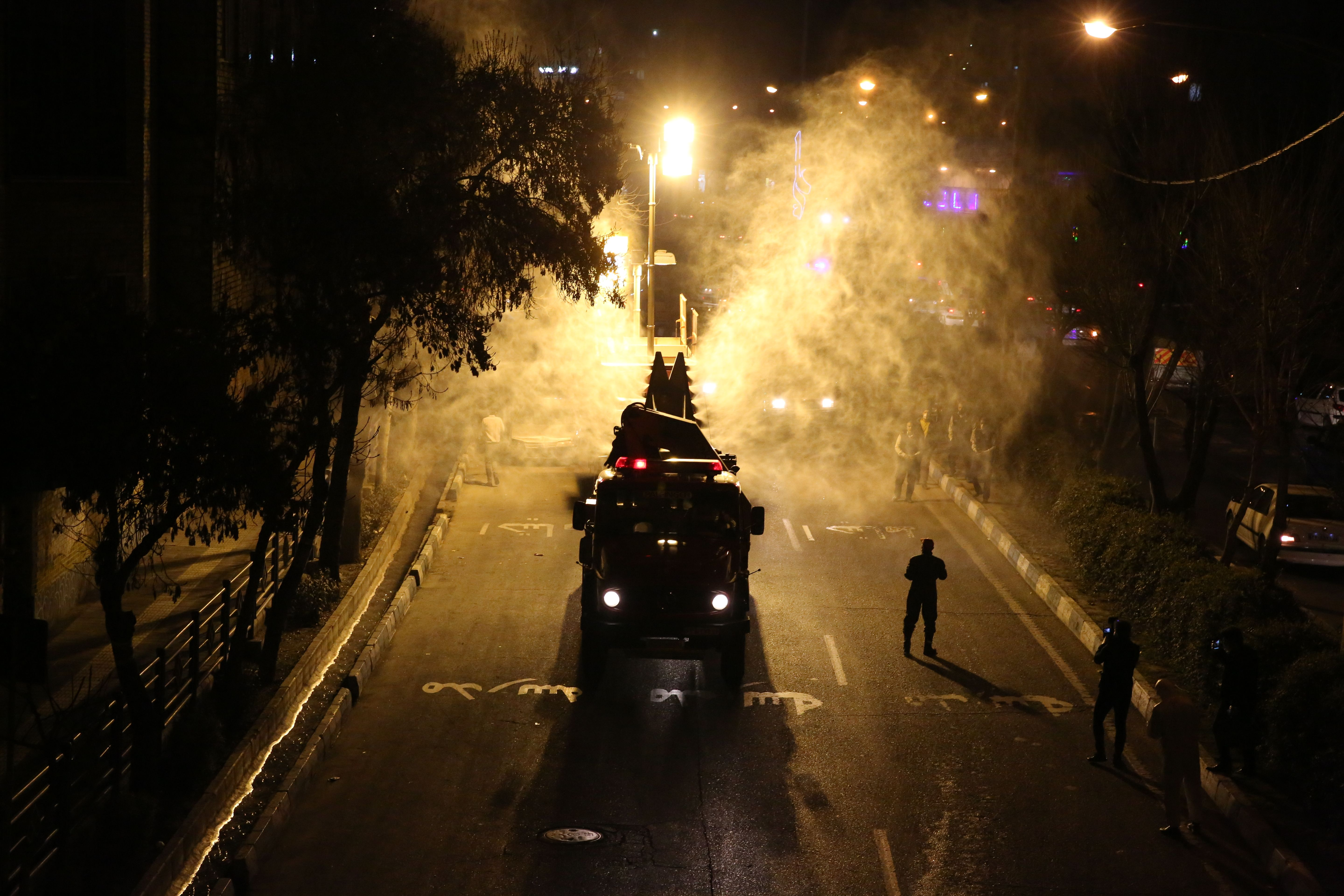 Iranian firefighters disinfect streets and alleys in southern Tehran to halt the spread of coronavirus on March 11.