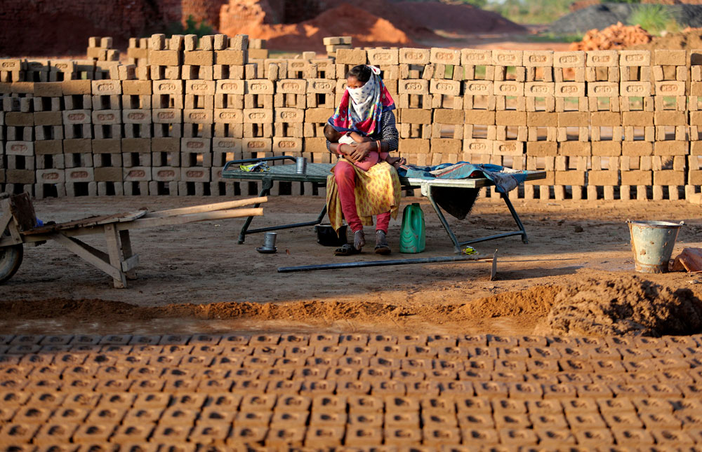 An laborer feeds her child at a brick kiln on the outskirts of Jammu, India, on Wednesday, April 22.