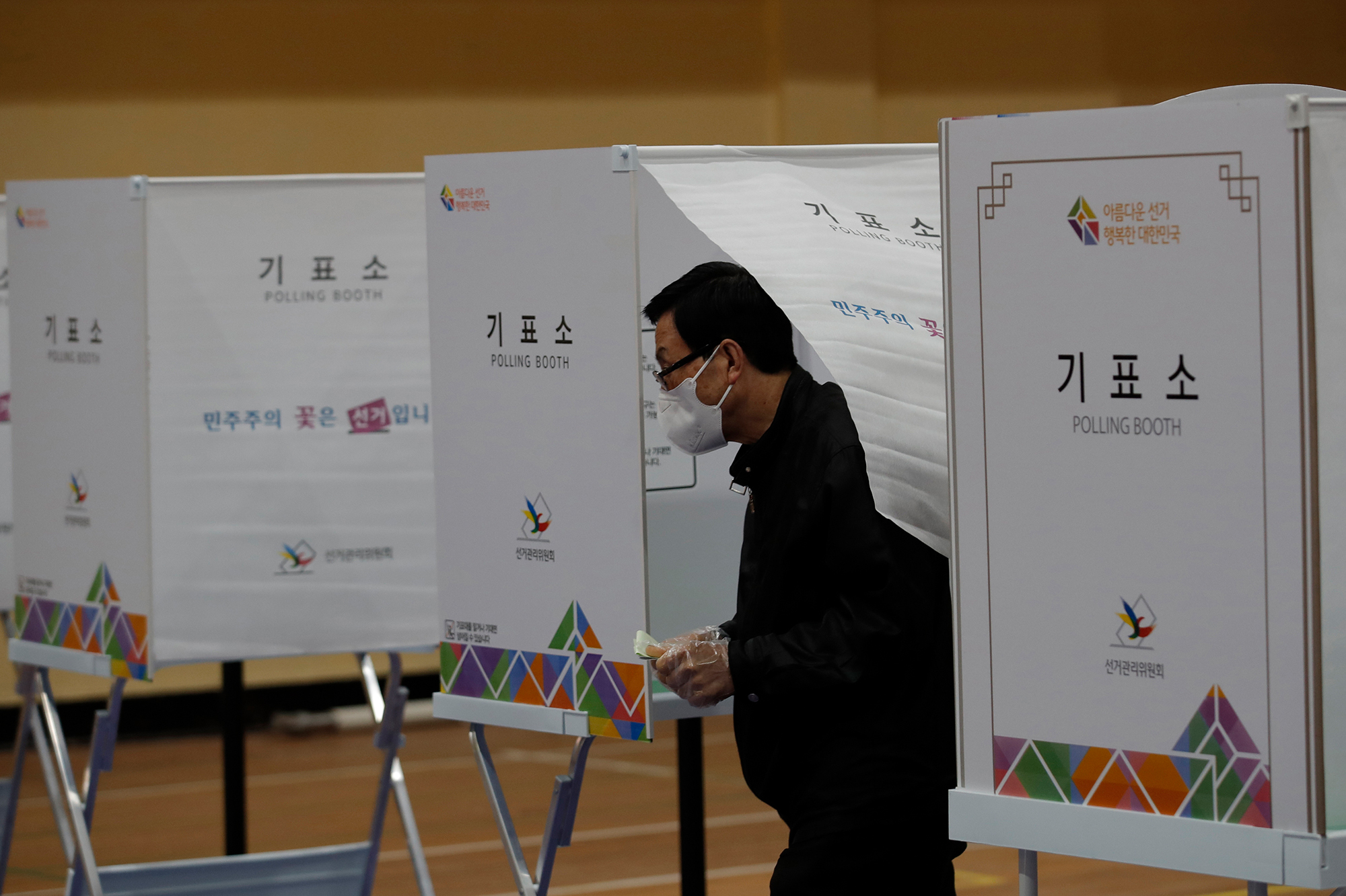 A voter wearing a face mask to help protect against the spread of the coronavirus exits out to cast his vote for the parliamentary election at a polling station in Seoul, South Korea, on Wednesday, April 15.