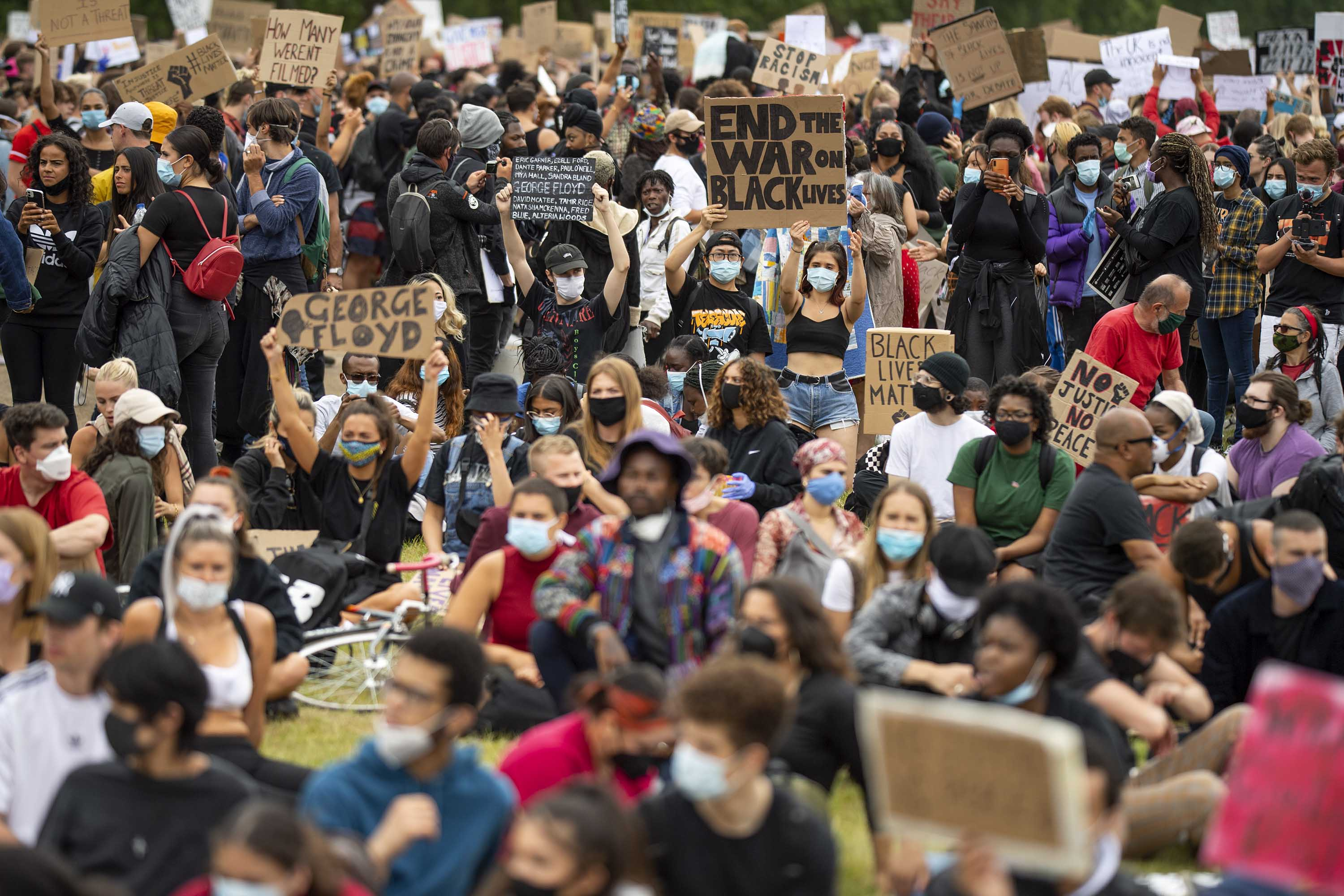 People hold up signs during a Black Lives Matter protest in London on June 3.