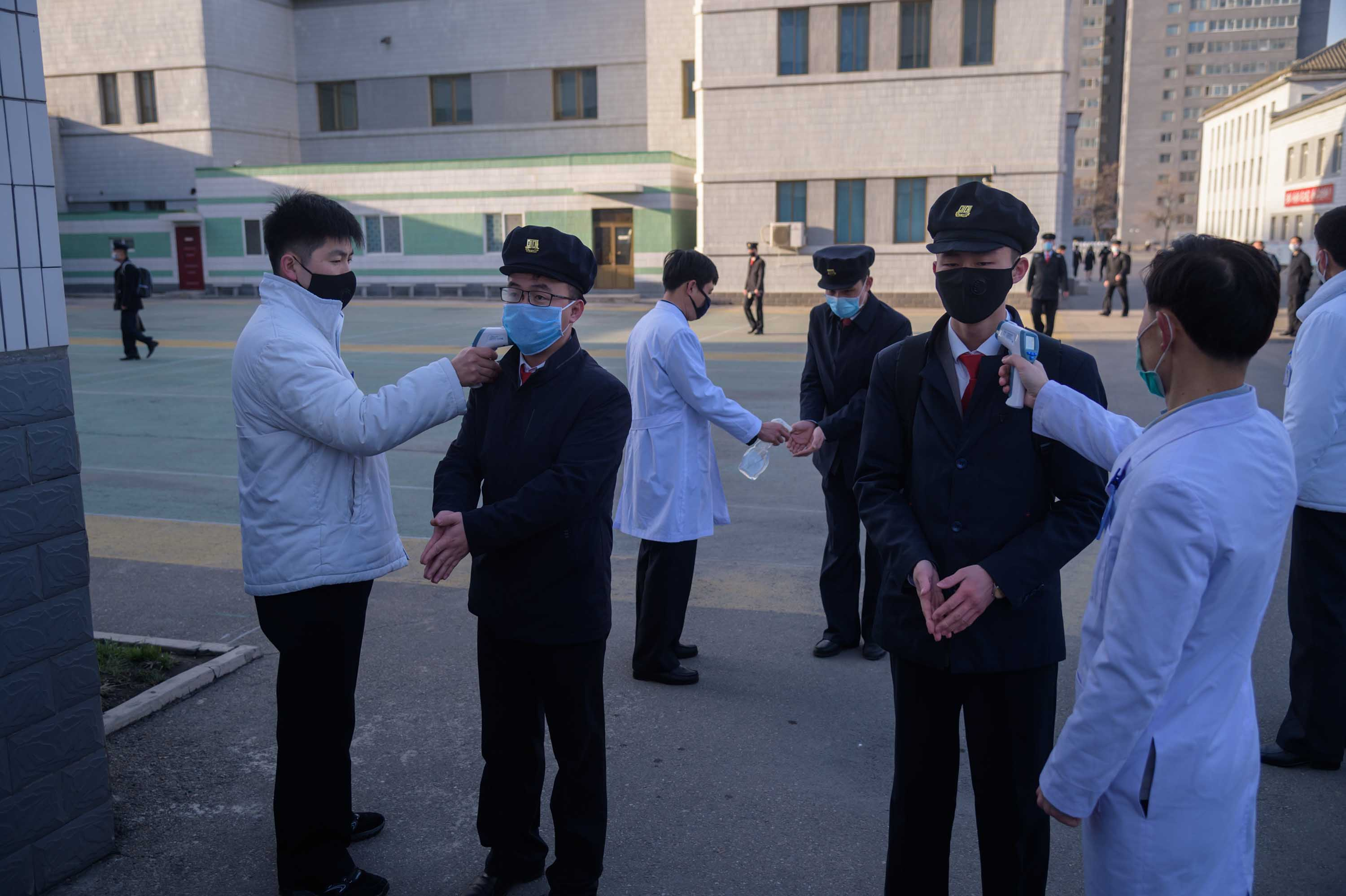 Students wearing face masks disinfect their hands and undergo a temperature check as they arrive for a lecture on preventative measures against coronavirus at the Pyongyang University of Medicine in Pyongyang, North Korea, on April 22.