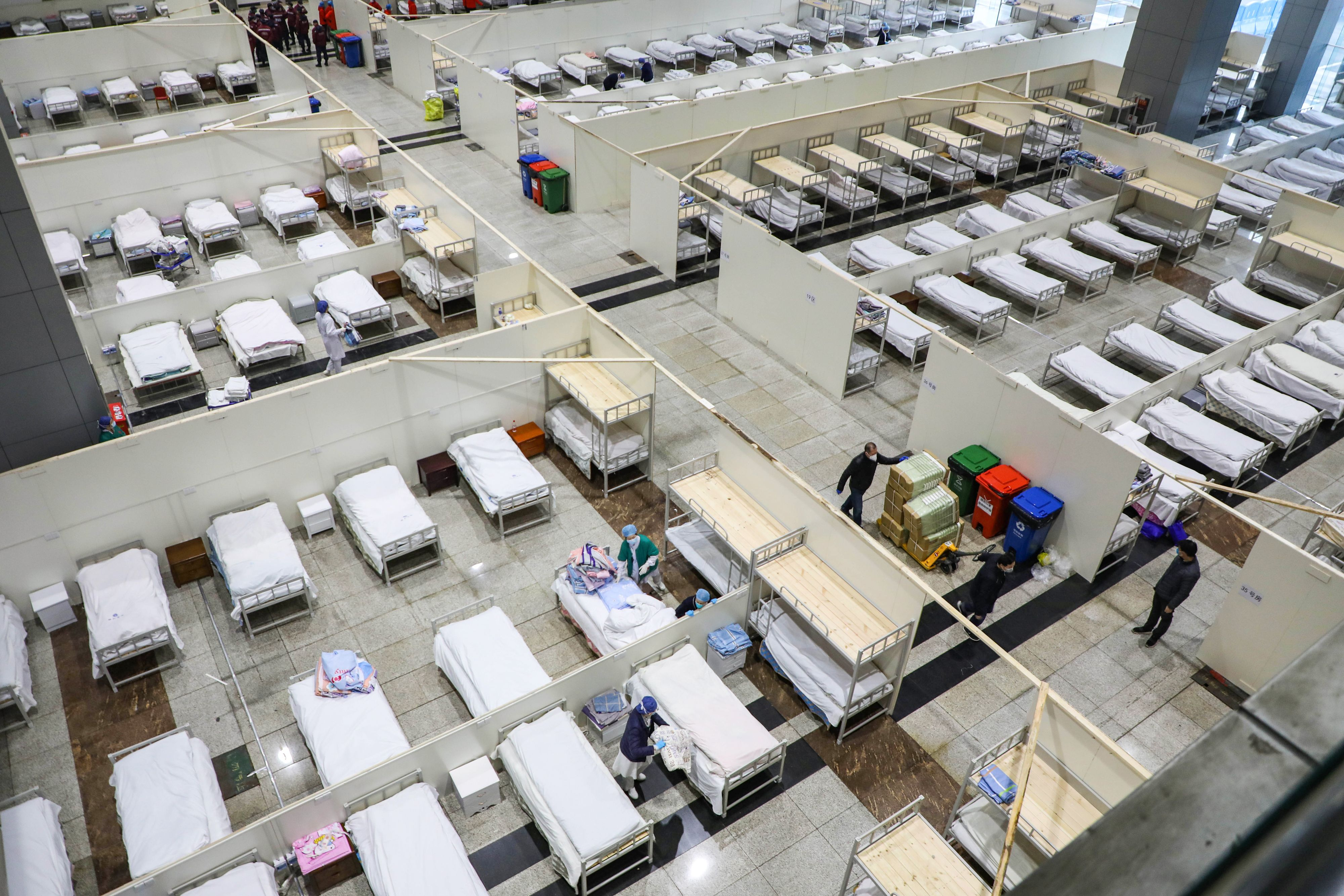 Medical staff preparing beds for patients at a converted hospital in Wuhan on Wednesday.