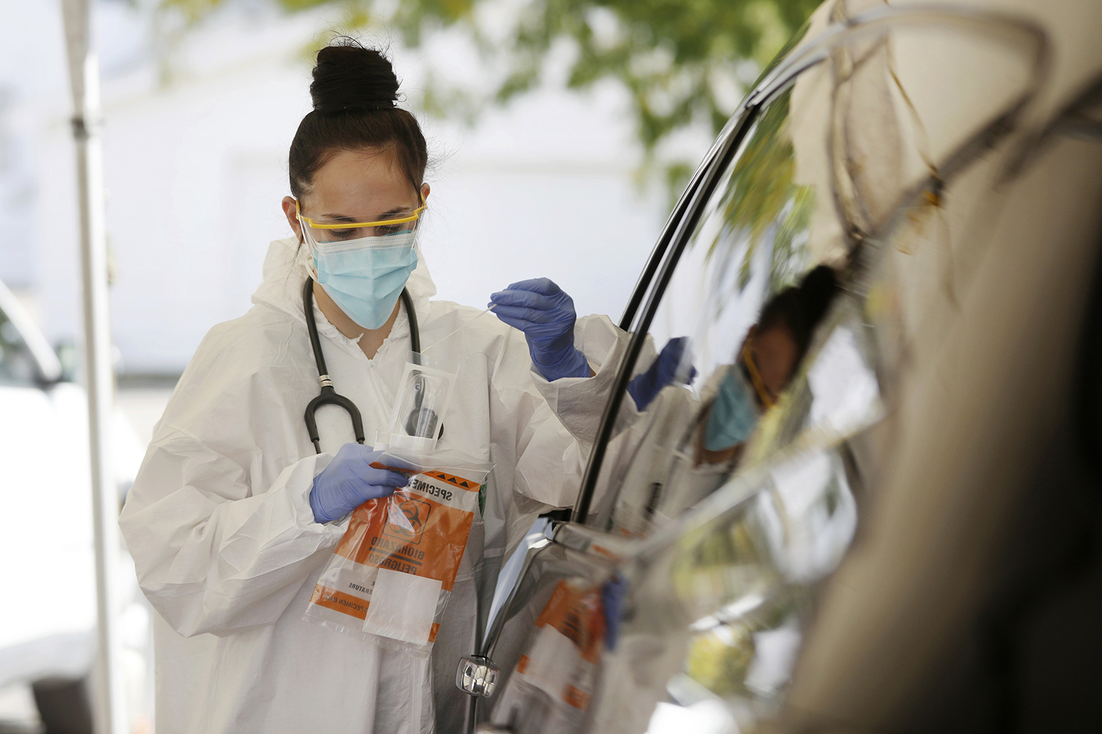 Medical Assistant Savannah Dela Vega places a nasal swab in a container for coronavirus testing at the drive-thru clinic in Casper, Wyoming, on Friday, October 9, 2020.