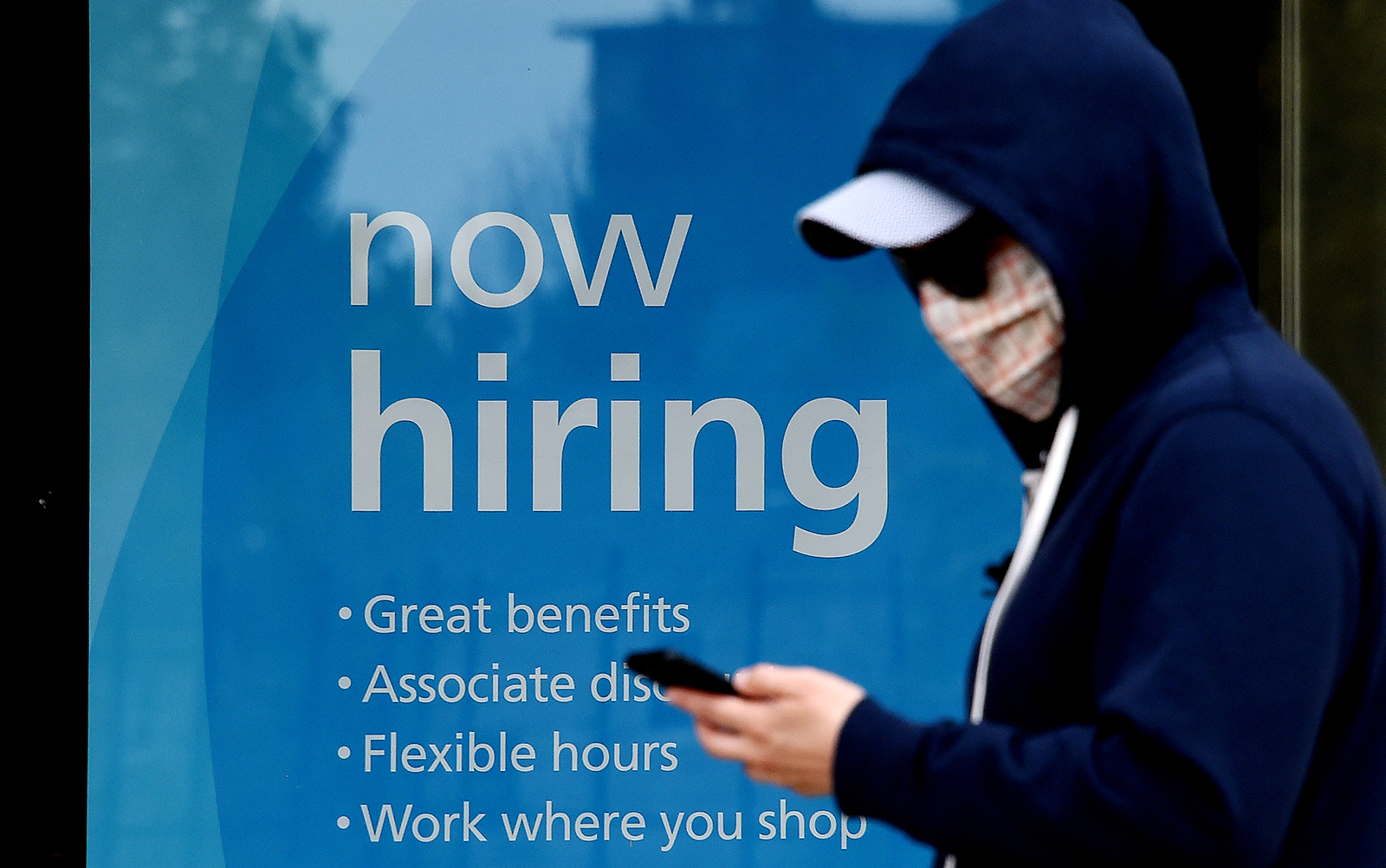 """A man wearing a face mask walks past a sign """"Now Hiring"""" in front of a store amid the coronavirus pandemic on May 14, in Arlington, Virginia."""