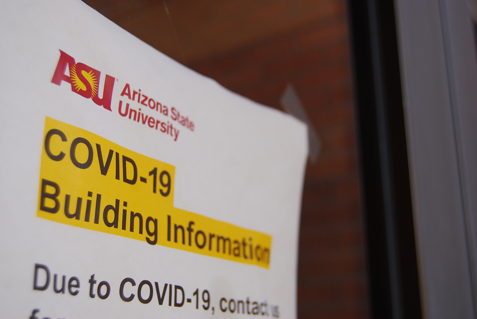 A sign is posted on the entrance to an Arizona State University building in Tempe, Arizona, on June 1.