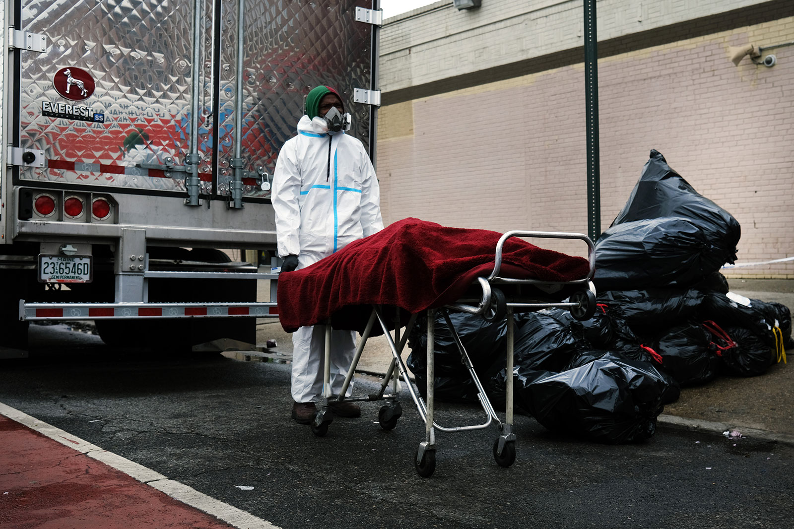 A body is moved from an unrefrigerated truck outside the Andrew Cleckley Funeral Home in Brooklyn, New York on April 30. The truck was being used to store bodies of coronavirus victims that the funeral home could not accommodate.