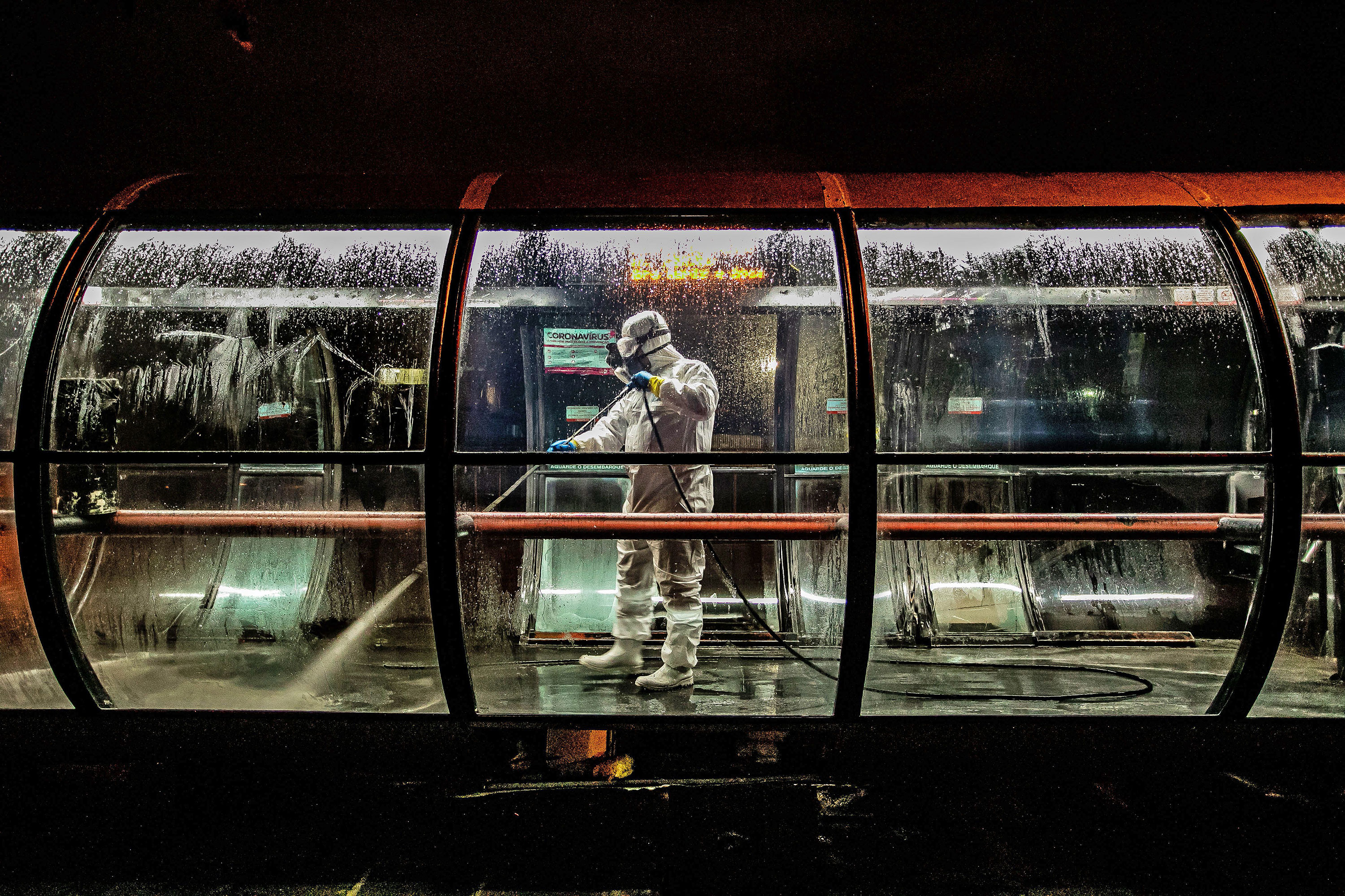 A volunteer worker disinfects a public bus station in Curitiba, Brazil on April 1.