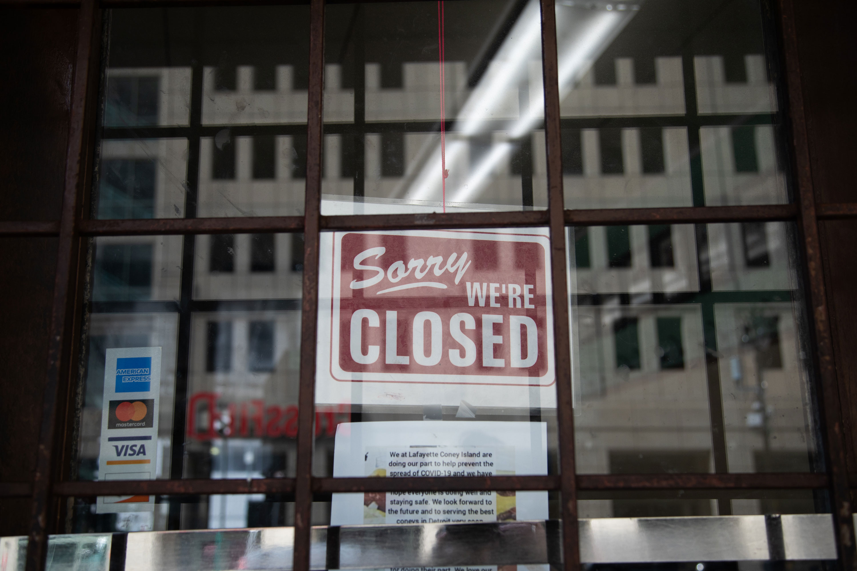 "A ""closed"" sign hangs on the door of a restaurant in Detroit in April."
