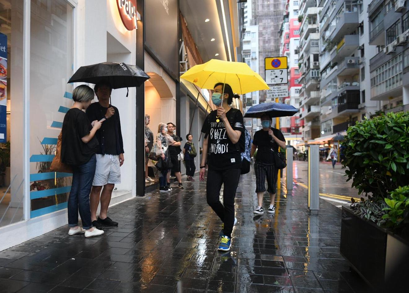 Protesters duck for cover from the rain in Hong Kong.