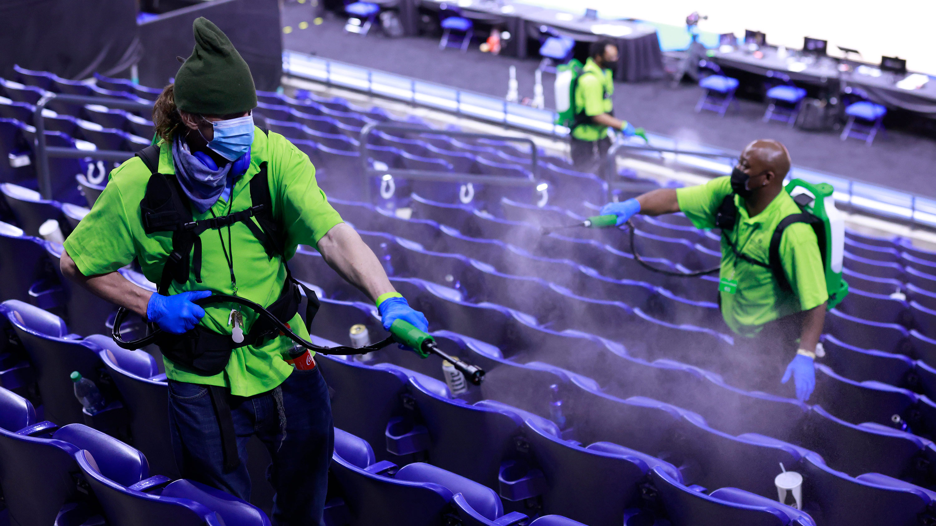 Employees disinfect seats ahead of a Purdue Boilermakers and Ohio State Buckeyes basketball game at Lucas Oil Stadium in Indianapolis, Indiana, on March 12.
