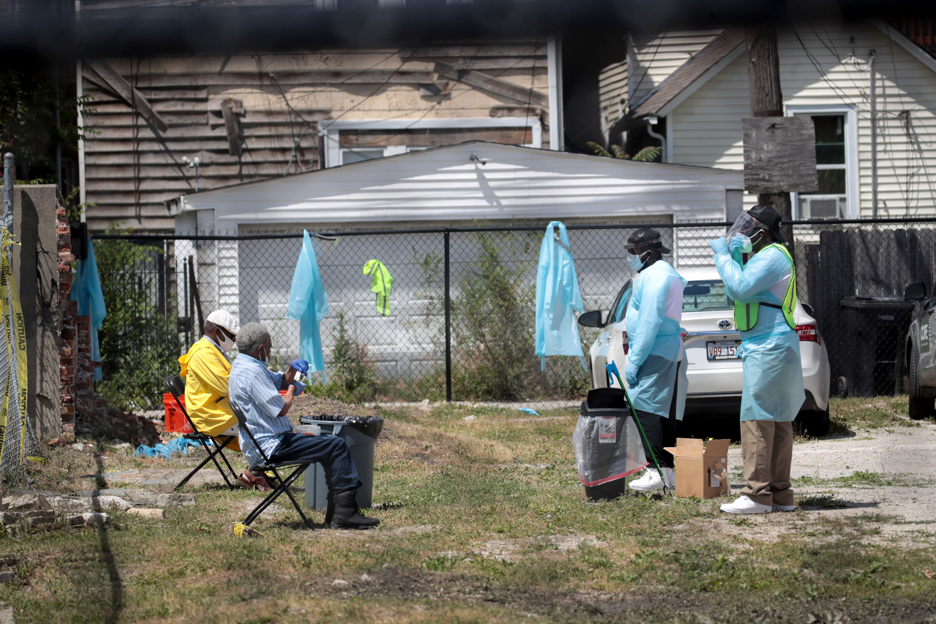Workers talk residents through a Covid-19 self-administered test on June 23 at a mobile testing site set up on a vacant lot in Chicago's Austin neighborhood.