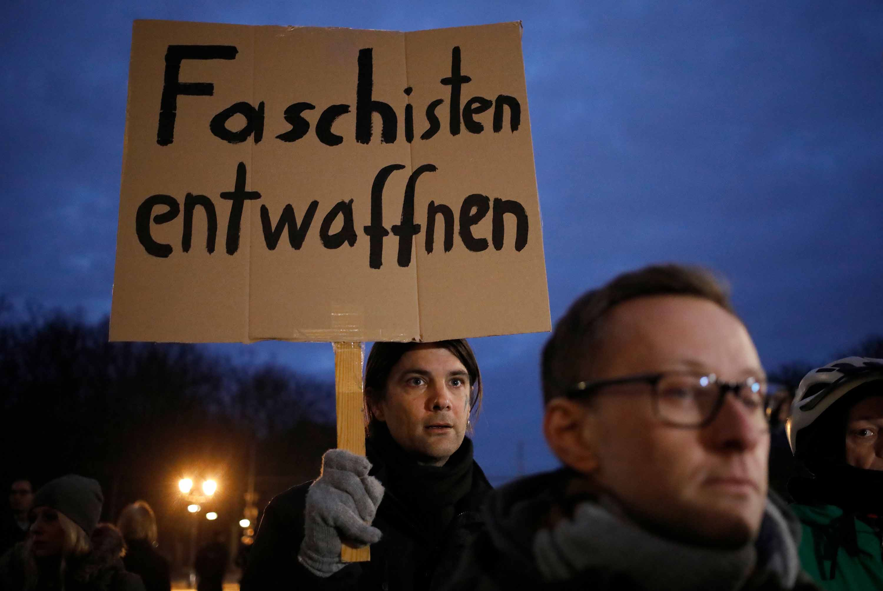 """A man holds a poster reading """"Disarm fascists"""" during the vigil at Brandenburg Gate."""