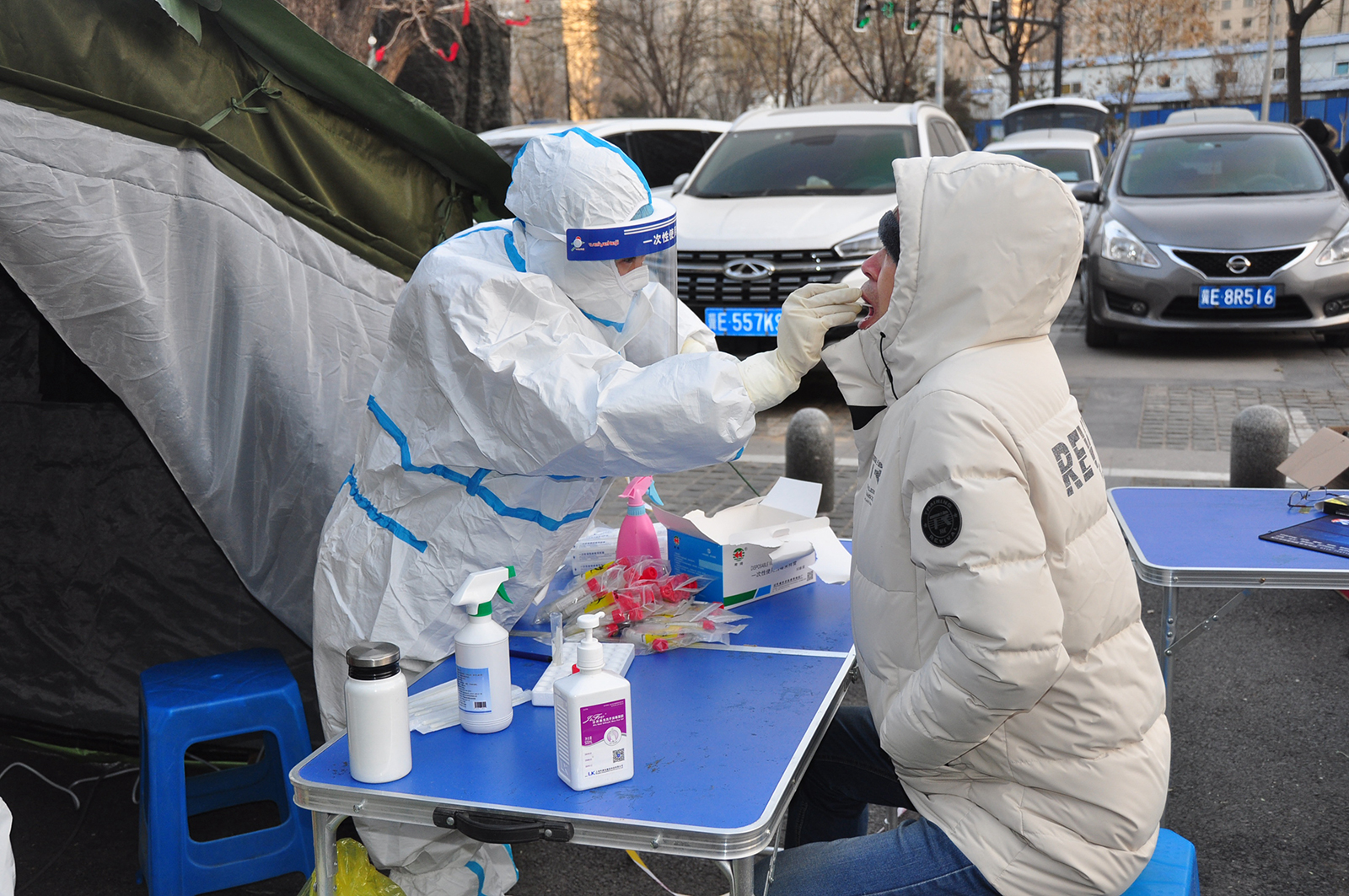 A medical worker wearing a protective suit collects a throat swab from a local resident for coronavirus (Covid-19) antigen rapid test at a temporary Covid-19 testing center in Xingtai, Hebei Province of China, on January 6.