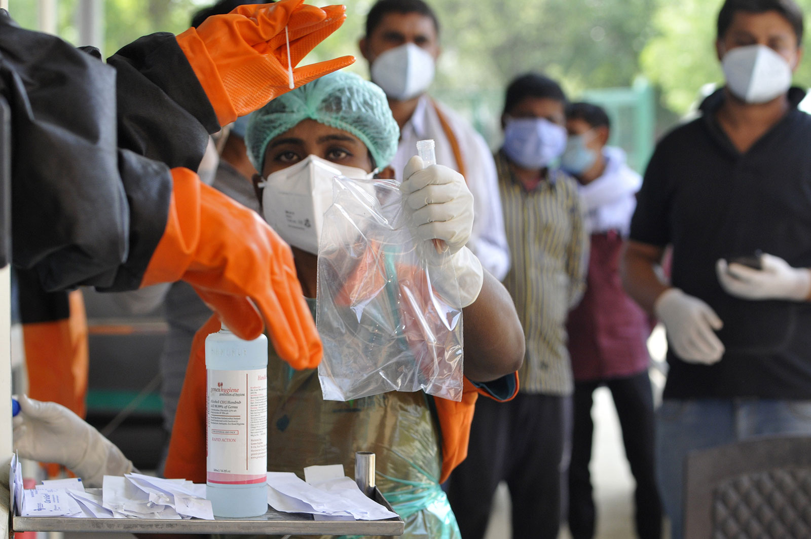 A medic handles a sample collected for Covid-19 testing at a booth outside Sharda Hospital in Greater Noida, India.