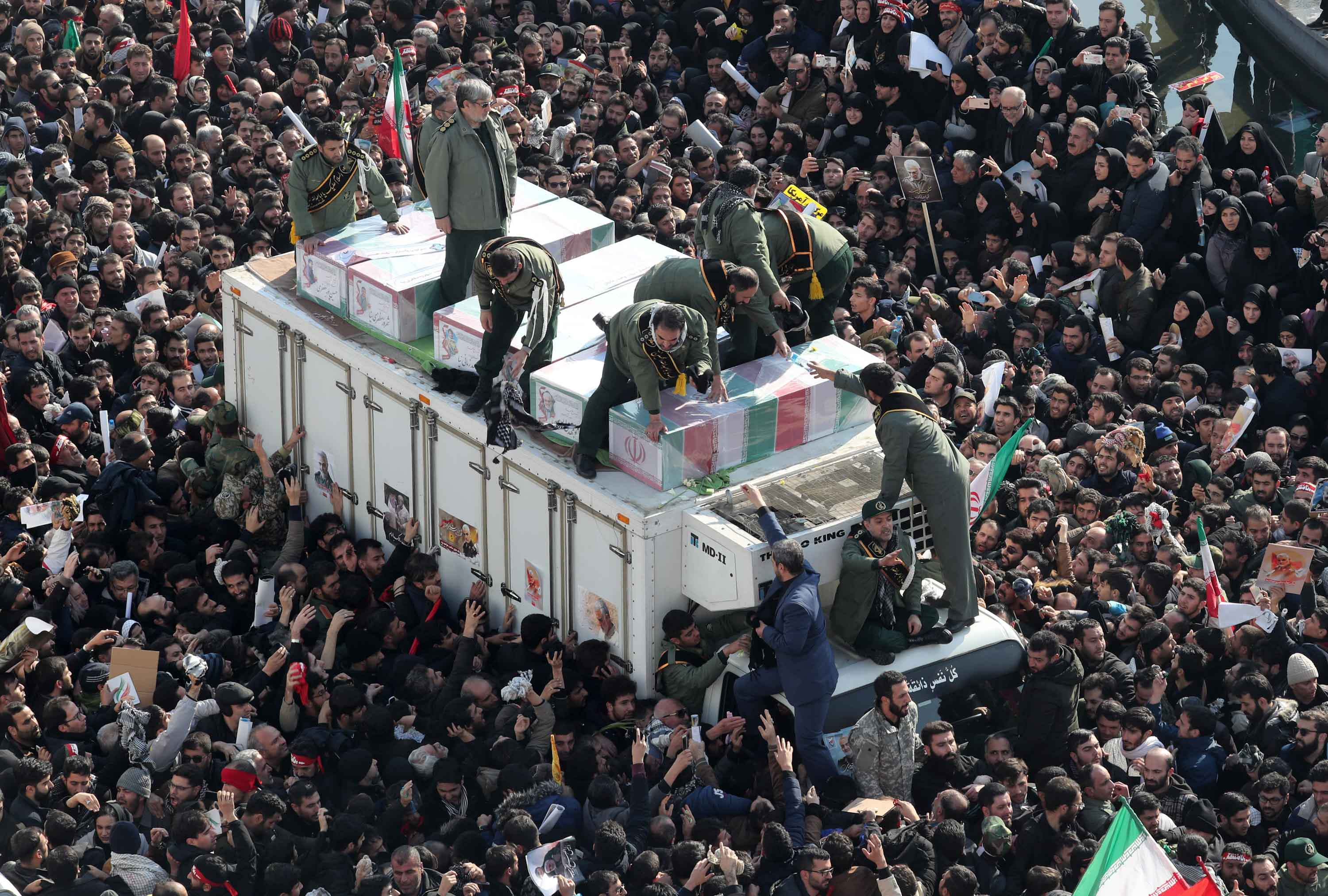 Iranians surround the coffins of Soleimani and others killed in a US airstrike in Baghdad on Friday.