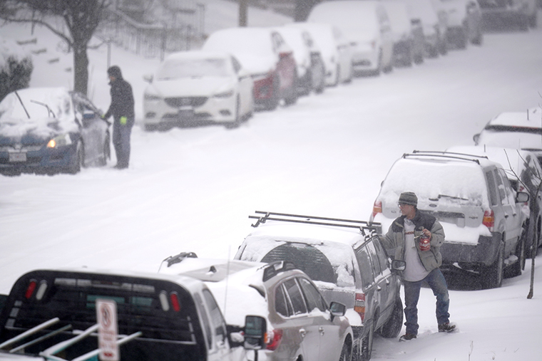 People clear snow off of cars Monday, February 15, in St. Louis. Missouri