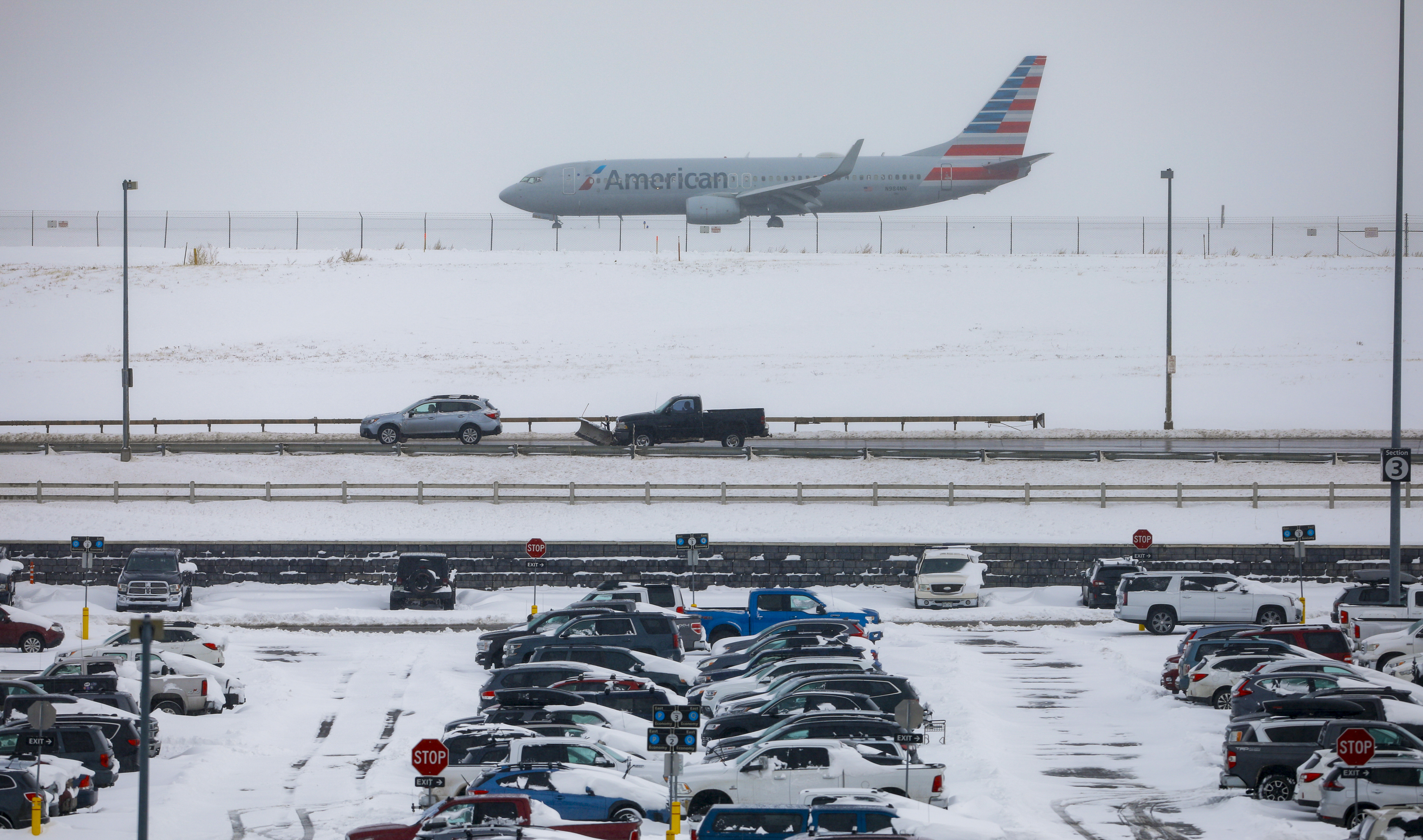 A jet passes snow-covered cars parked at Denver International Airport on November 26, 2019 in Denver, Colorado.