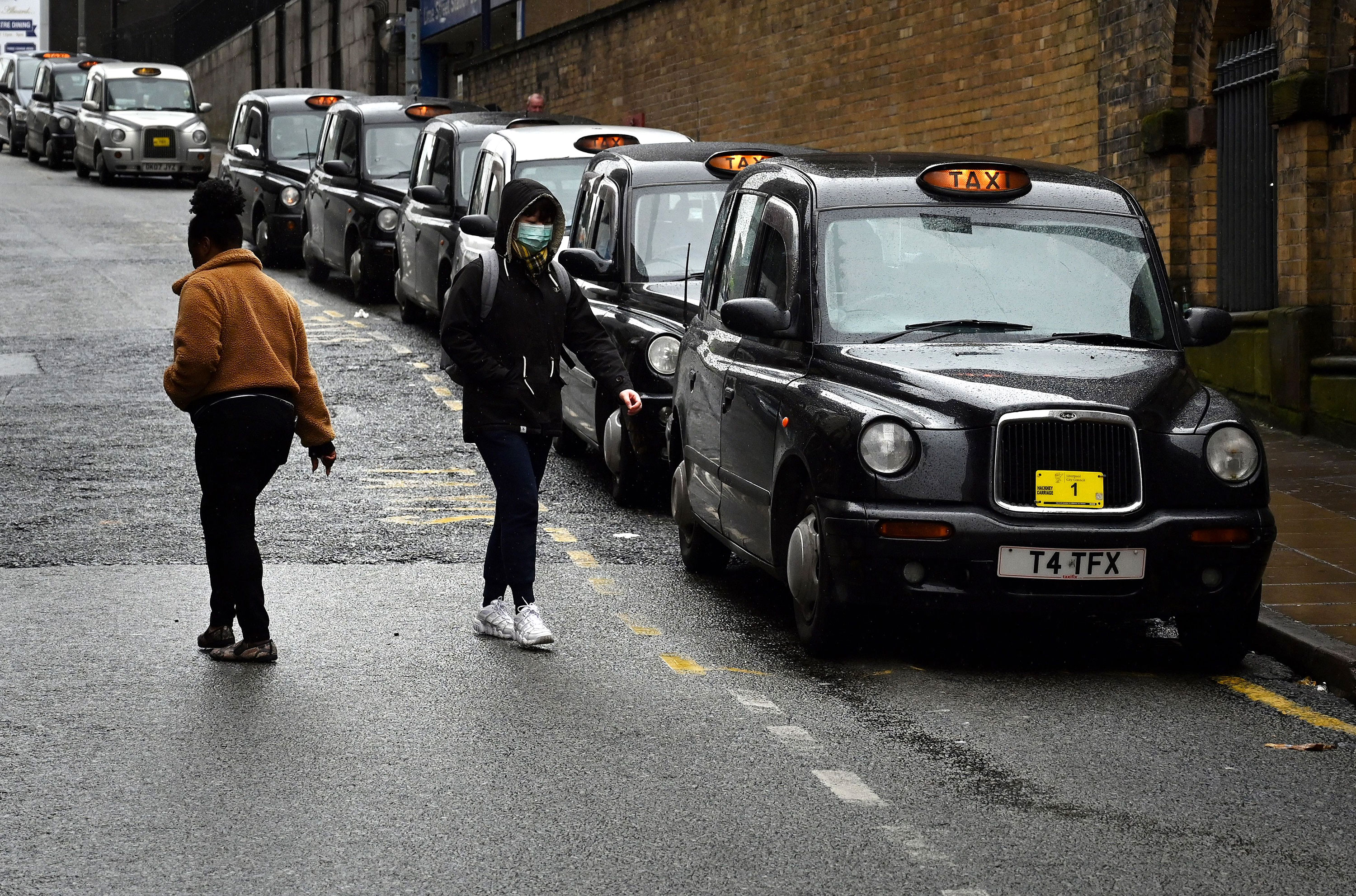 Pedestrians walk past a line of taxis on March 18 in Liverpool, England.