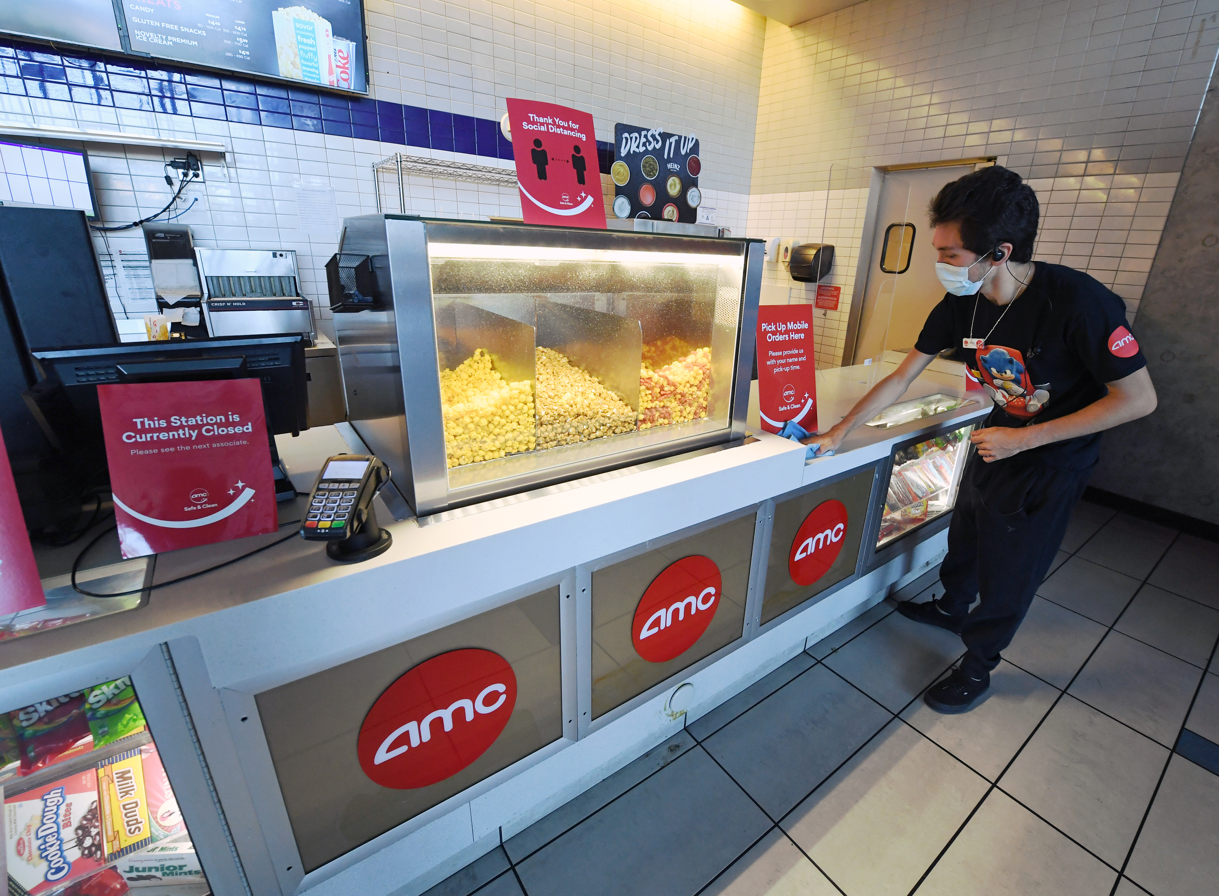 An employee sanitizes the concession stand at AMC Town Square 18 on Thursday, August 20, in Las Vegas.