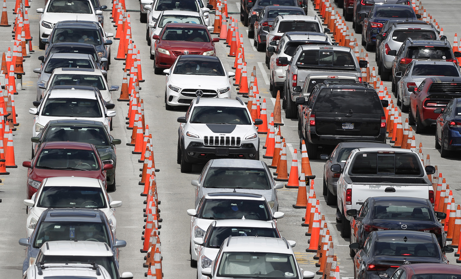 Lines of cars wait at a coronavirus testing site outside of Hard Rock Stadium, Friday, June 26, in Miami Gardens, Florida