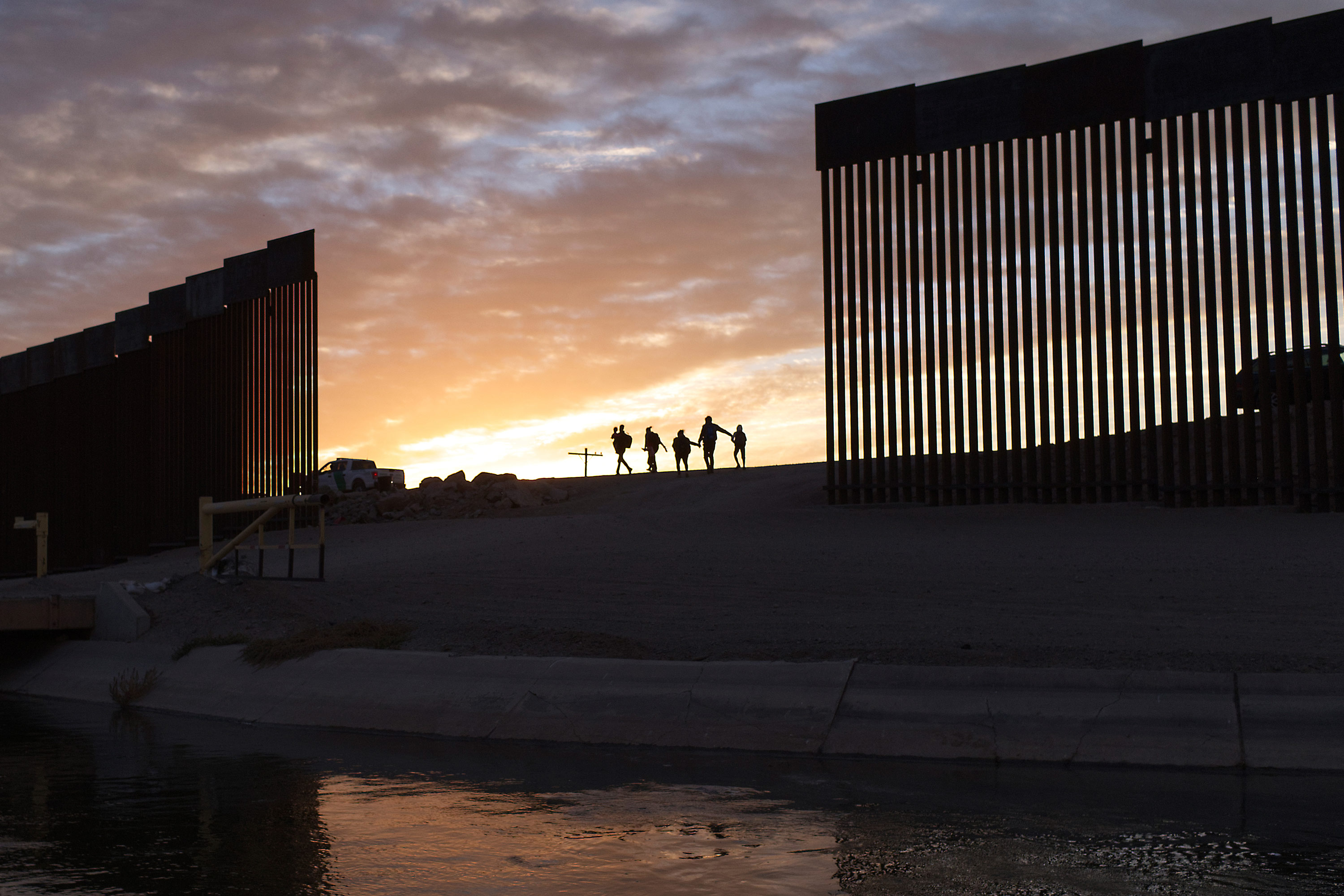 A pair of migrant families from Brazil pass through a gap in the border wall to reach the United States after crossing from Mexico to Yuma, Arizona, to seek asylum on June 10.