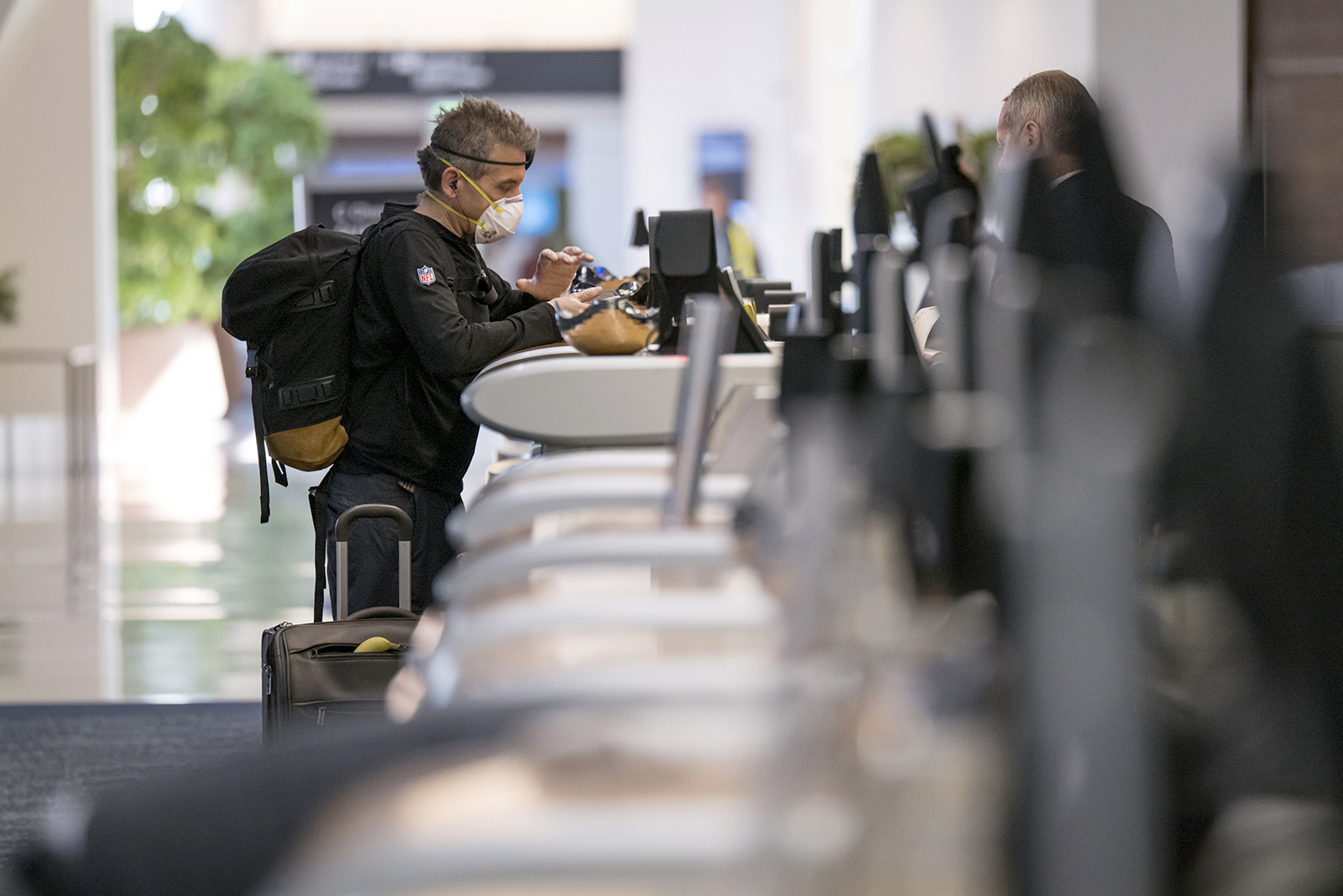 A traveler wearing a protective mask and gloves checks in at the Delta Air Lines Inc., counter at San Francisco International Airport in California on April 2.