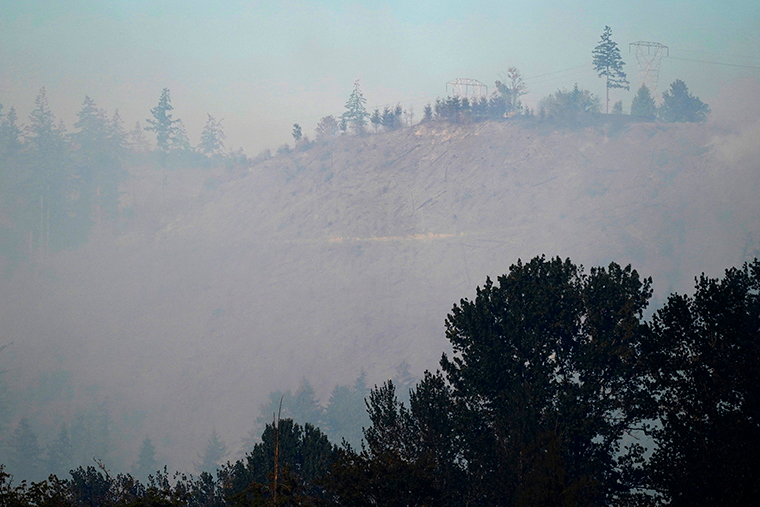 Smoke rises from a hillside burned by a wildfire, Tuesday, September 8, near Sumner, Washington.
