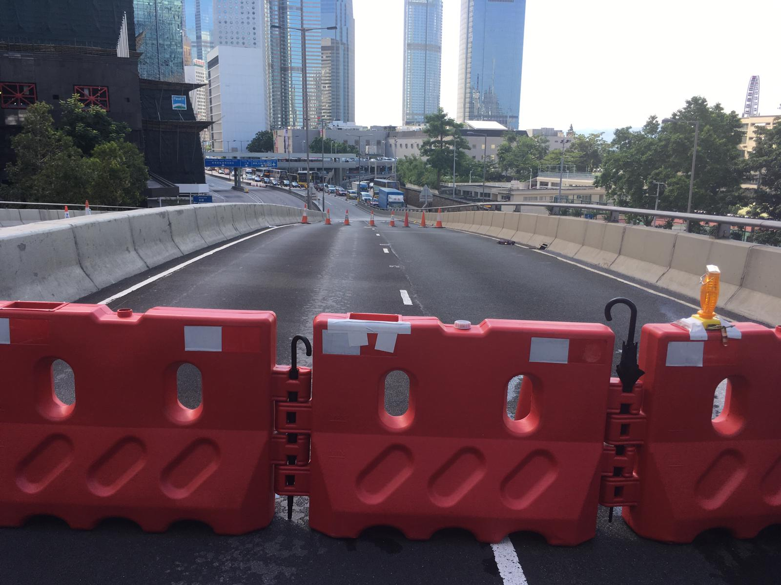 Protesters on Harcourt Road are building road blocks using umbrellas as makeshift joiners.