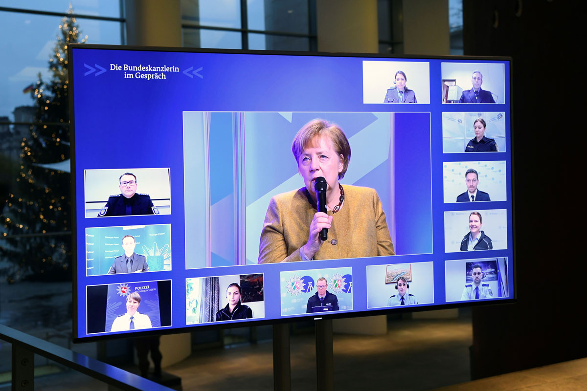 German Chancellor Angela Merkel is seen on a screen as she attends a virtual meeting with police officers at the Chancellery in Berlin on Nov. 30.