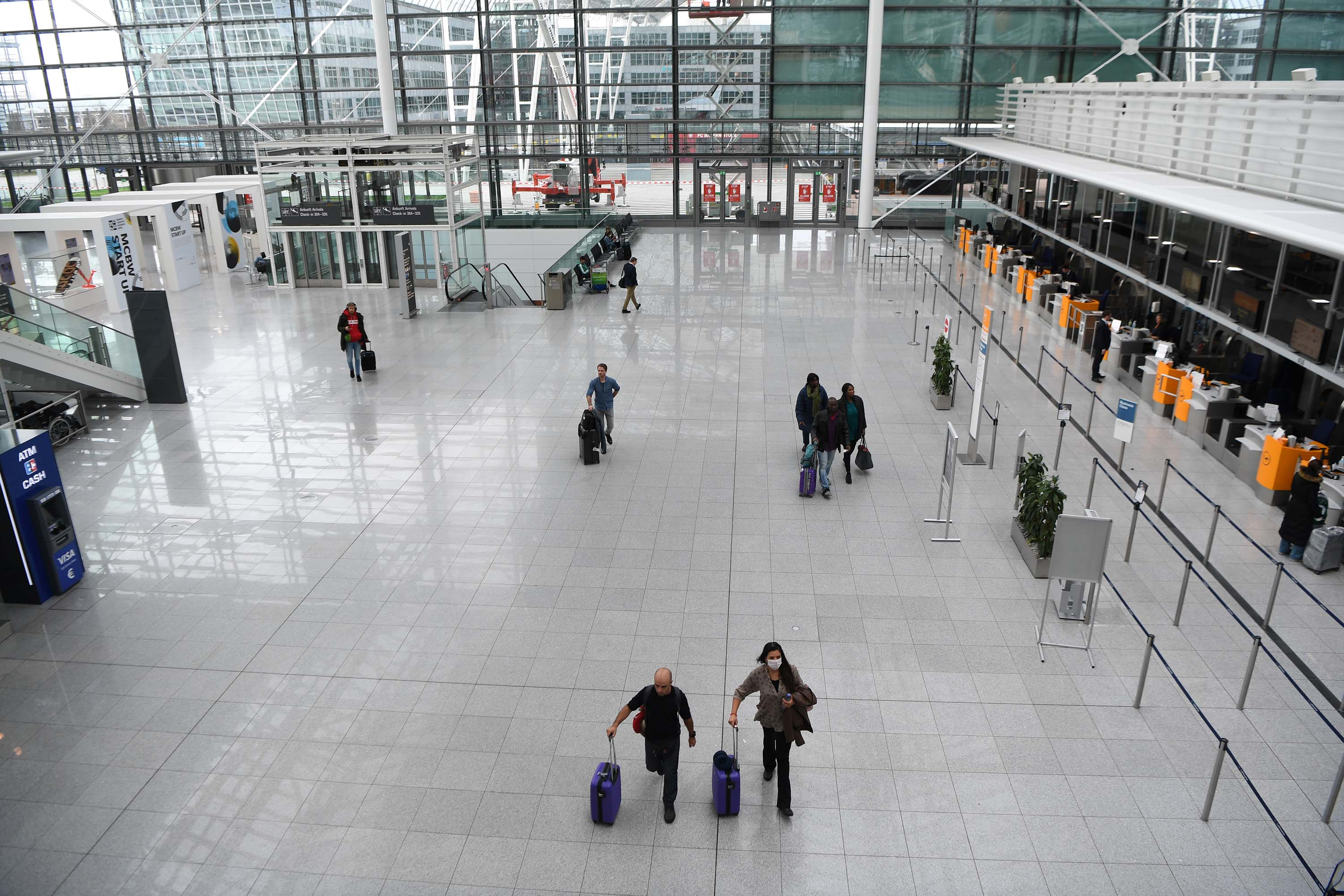 Travelers walk through Munich International Airport on March 17, in Freising, Germany.