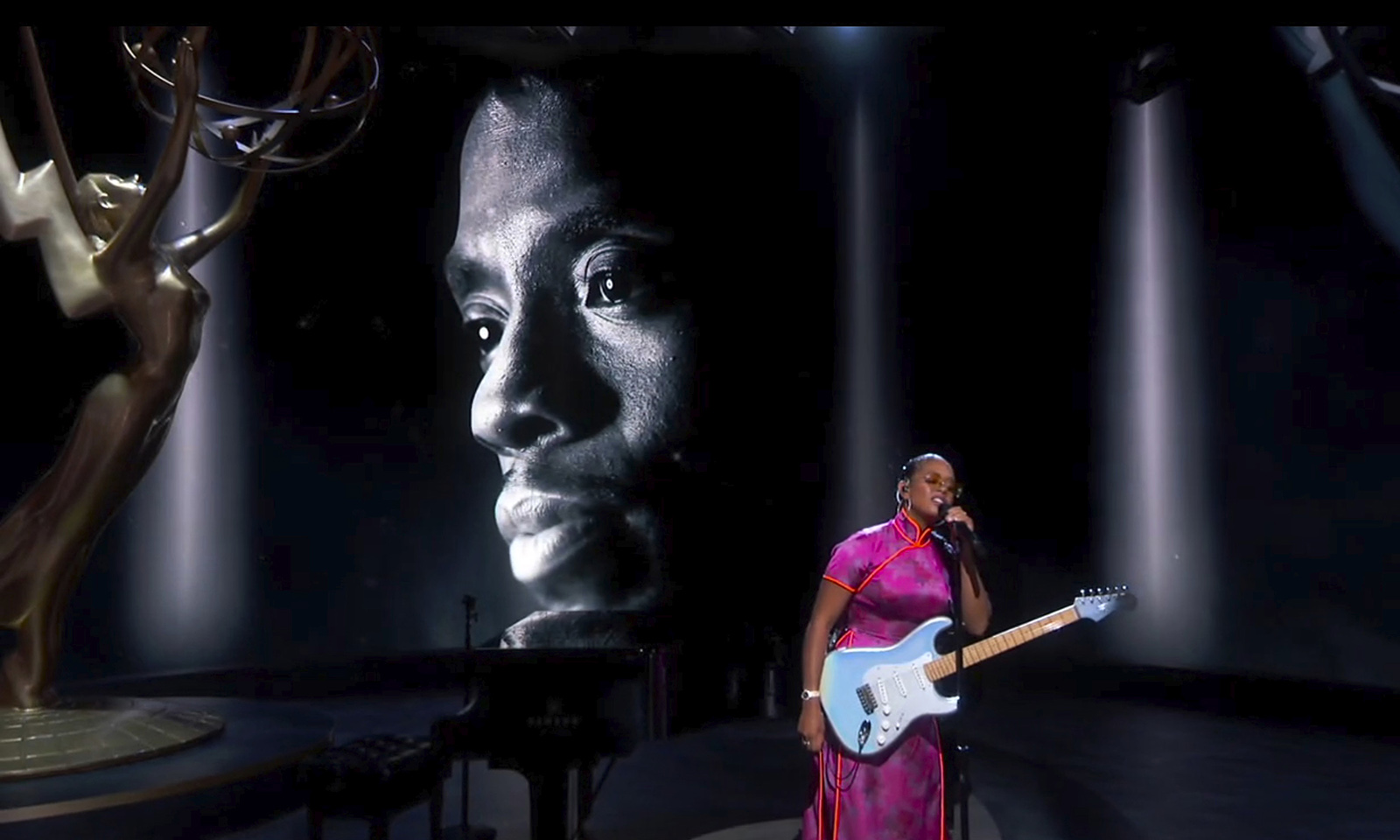 "In this video grab captured on Sept. 20, 2020, courtesy of the Academy of Television Arts & Sciences and ABC Entertainment, H.E.R. performs ""Nothing Compares 2 U"" during an In Memoriam tribute as the late actor Chadwick Boseman appears on screen during the 72nd Emmy Awards broadcast."