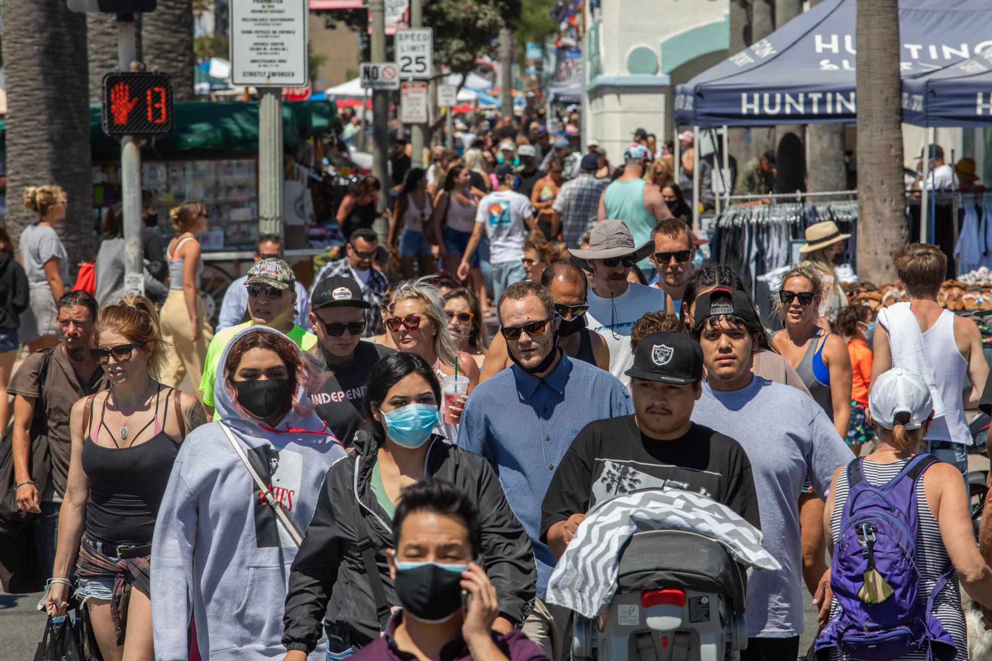 People cross the street in Huntington Beach, California, on July 19.