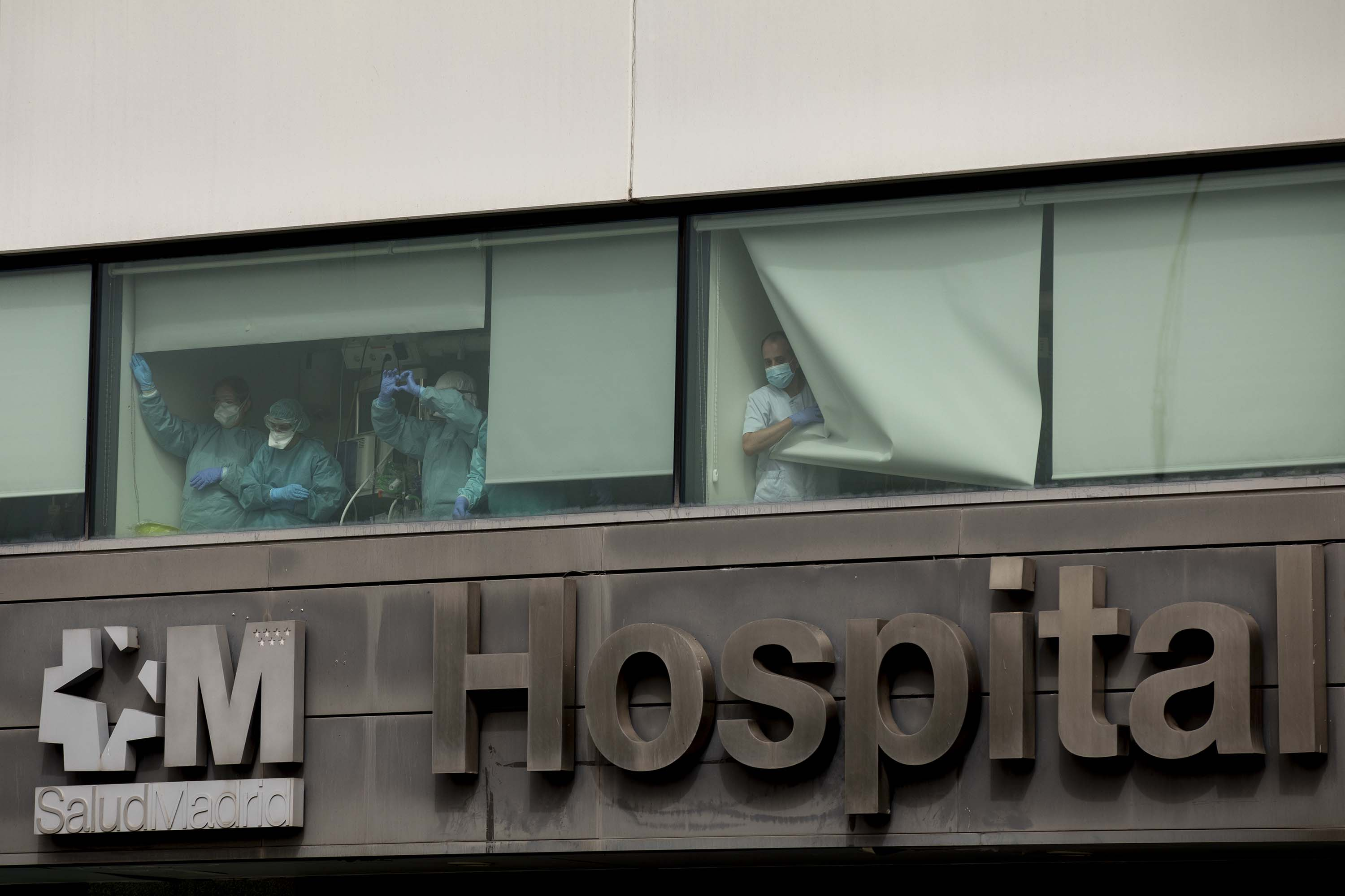 Medical staff wave from a window at La Paz Hospital in Madrid, Spain, on March 18, as the country works to stop the spread of the coronavirus.