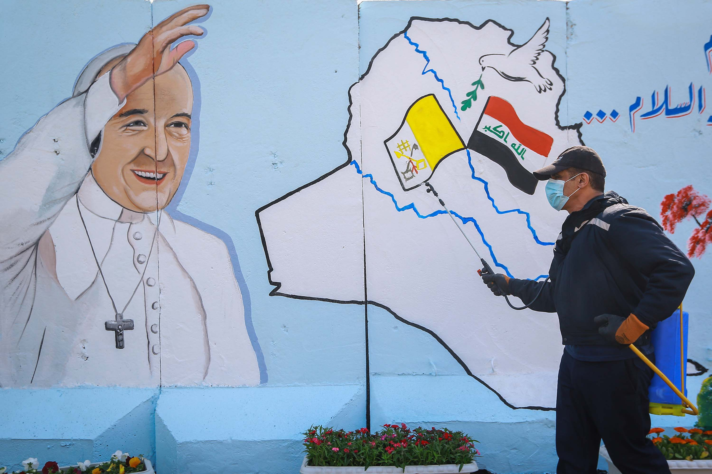 An Iraqi civil defence worker sprays disinfectant in front of a mural depicting Pope Francis at the Syriac Catholic Church of Our Lady of Salvation in Baghdad, Iraq, on March 2.