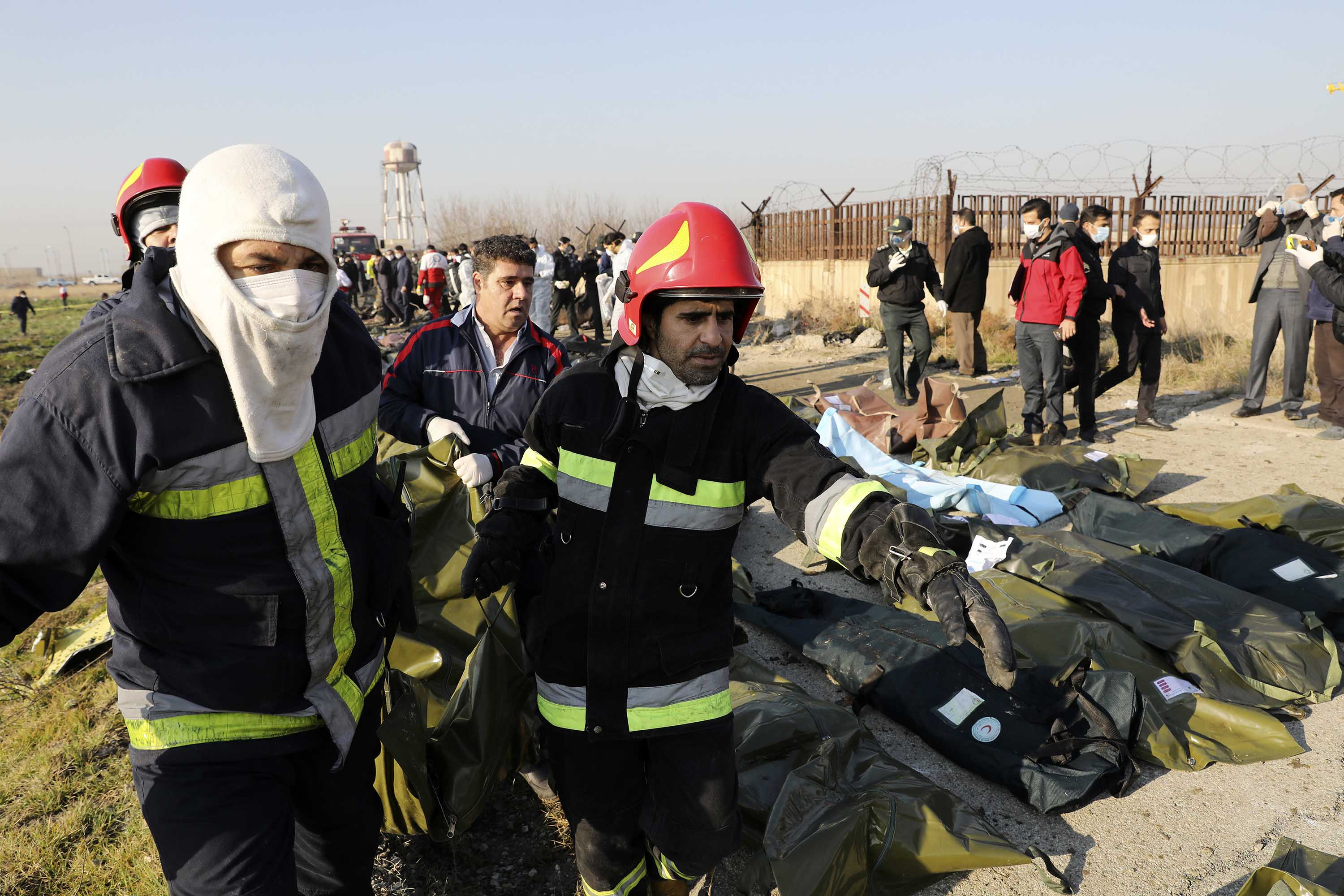 Rescue workers carry victims' remains at the crash site.