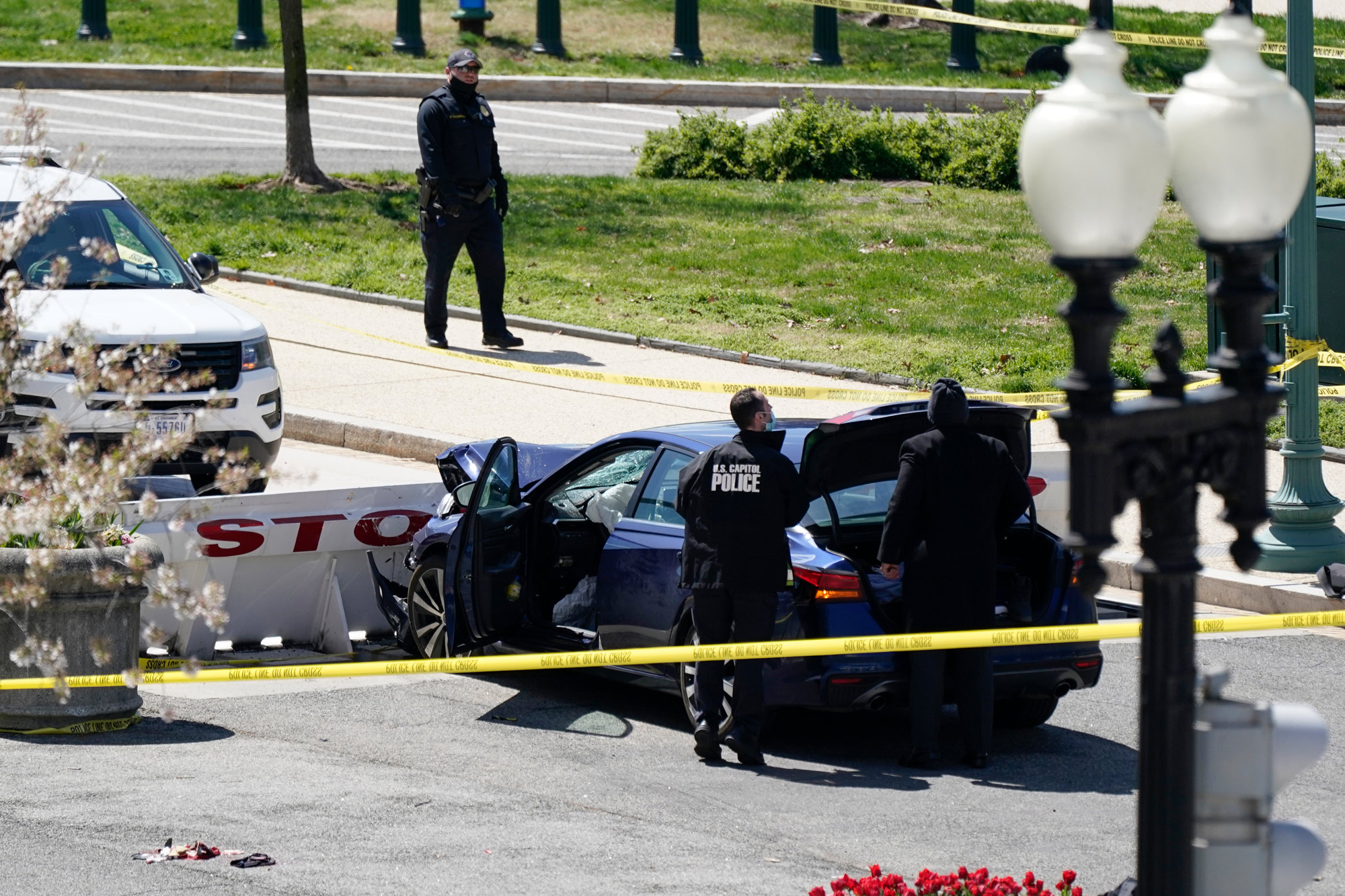 U.S. Capitol Police officers stand near a car that crashed into a barrier on Capitol Hill in Washington, DC, on April 2.