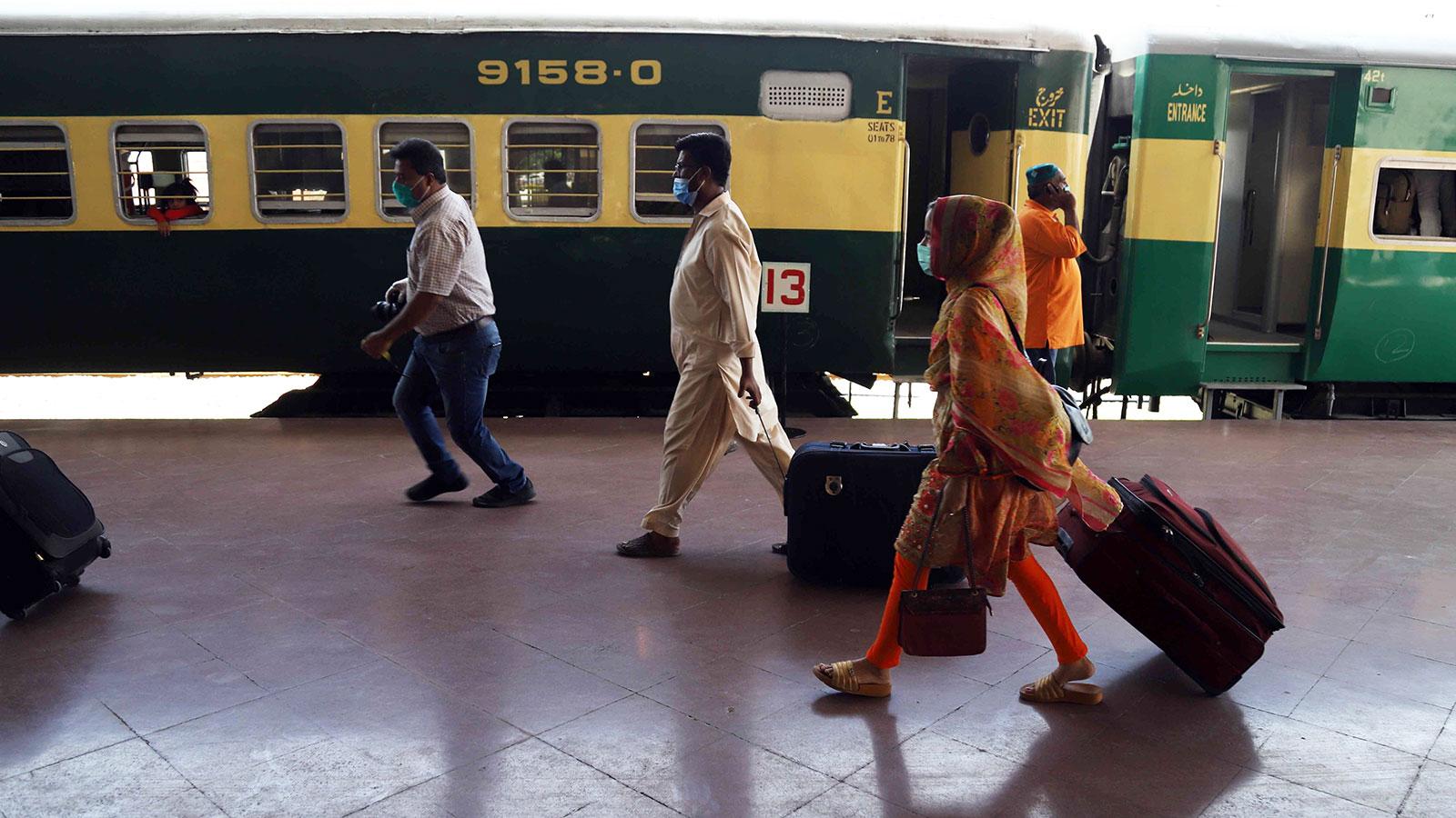 Passengers wearing face masks as a precaution against coronavirus arrive at Rawalpindi railway station in Pakistan on Wednesday.