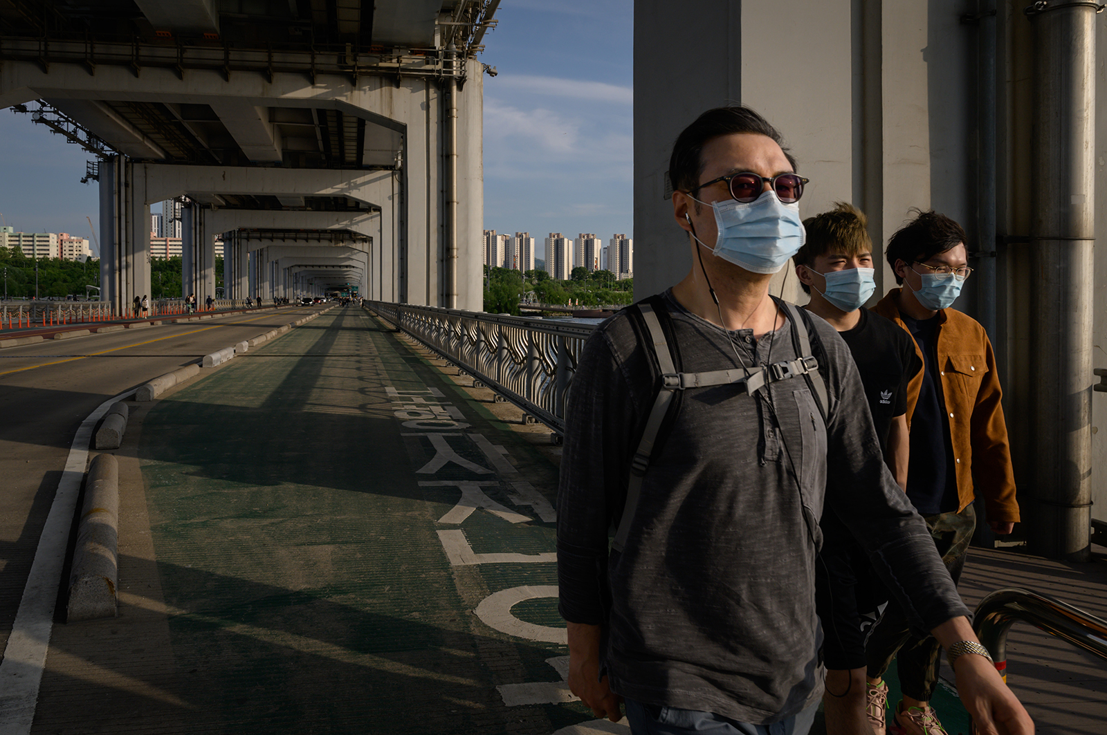 People wearing face masks walk along a bridge across the Han River on May 24, in Seoul.