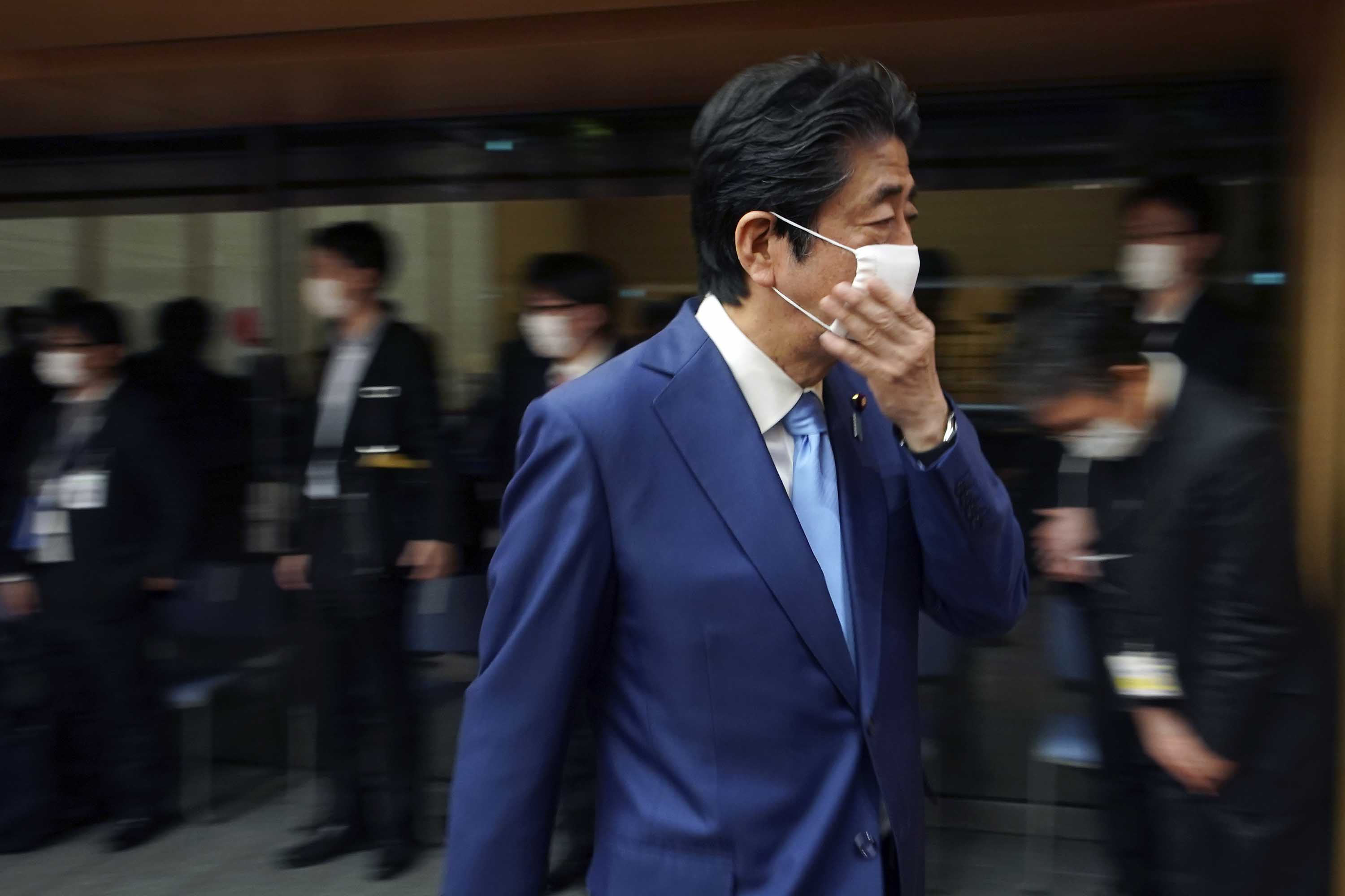 Japanese Prime Minister Shinzo Abe adjusts his face mask as he leaves a press conference in Tokyo on May 4.