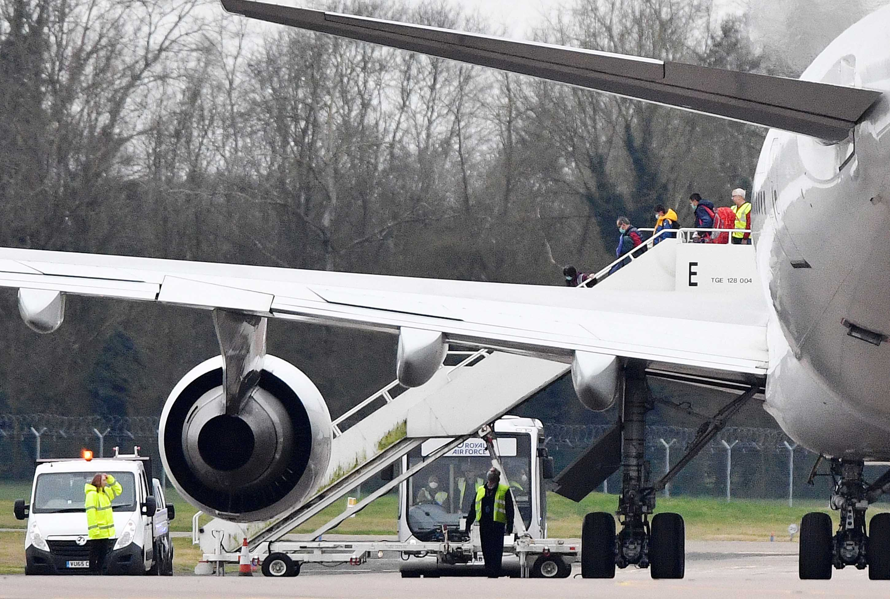 Some of the 83 Britons and 27 foreign nationals who were evacuated from Wuhan disembark a plane at RAF Brize Norton in England on Friday.