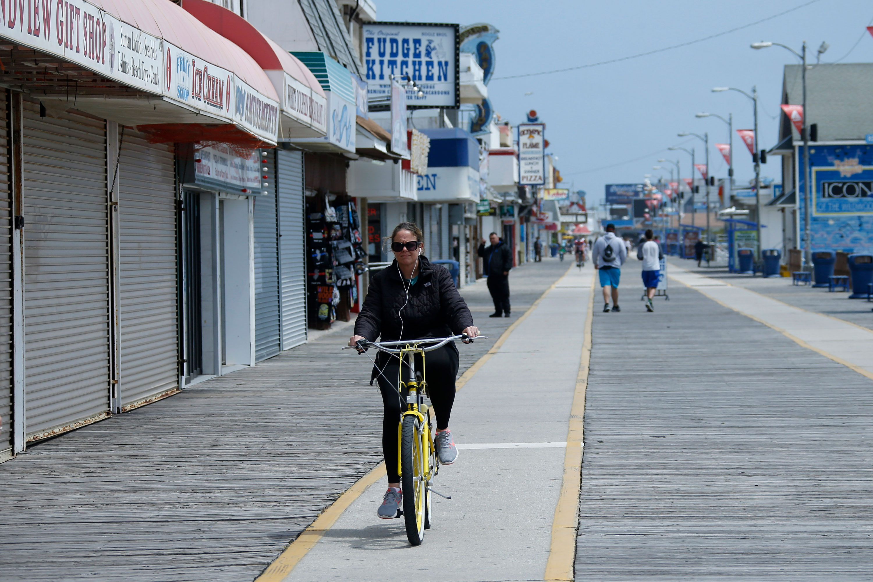 A woman rides a bike down the boardwalk on May 21 in Wildwood, New Jersey.