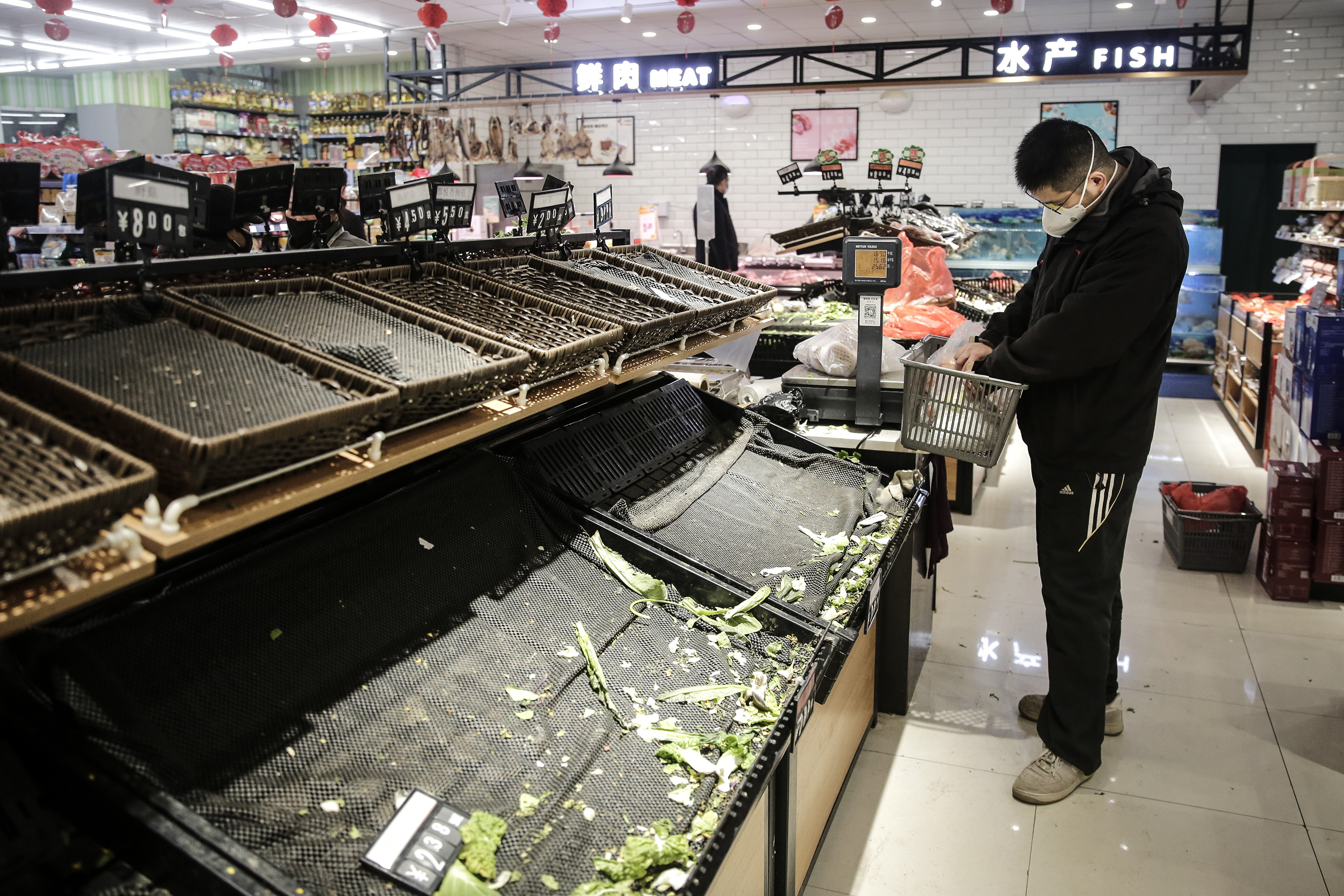 A resident wearing a mask shops for vegetables in Wuhan on January 23. Getty Images